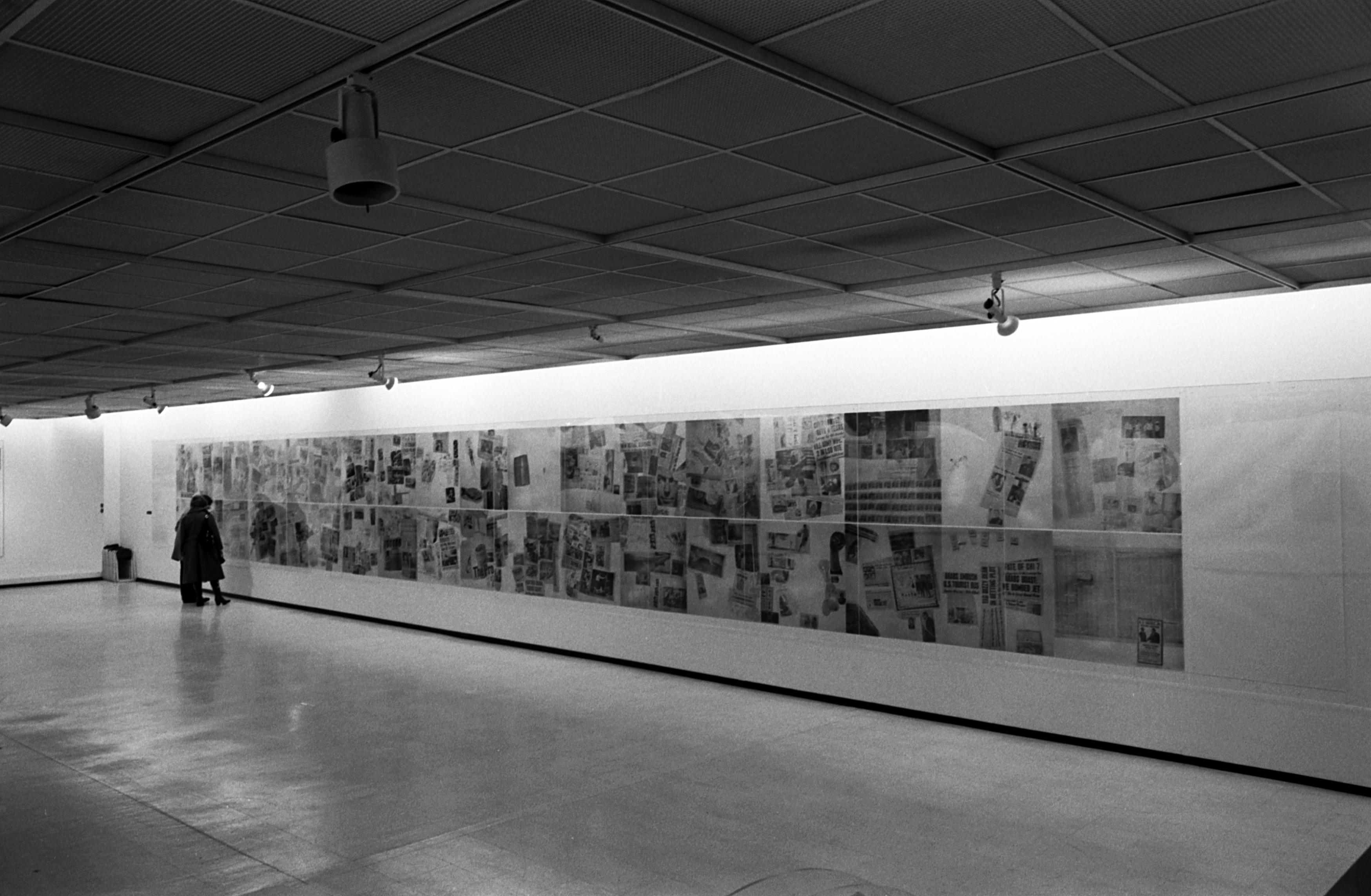 A black-and-white photo shows an installation view of dozens of graphic artworks. Two people view the works.