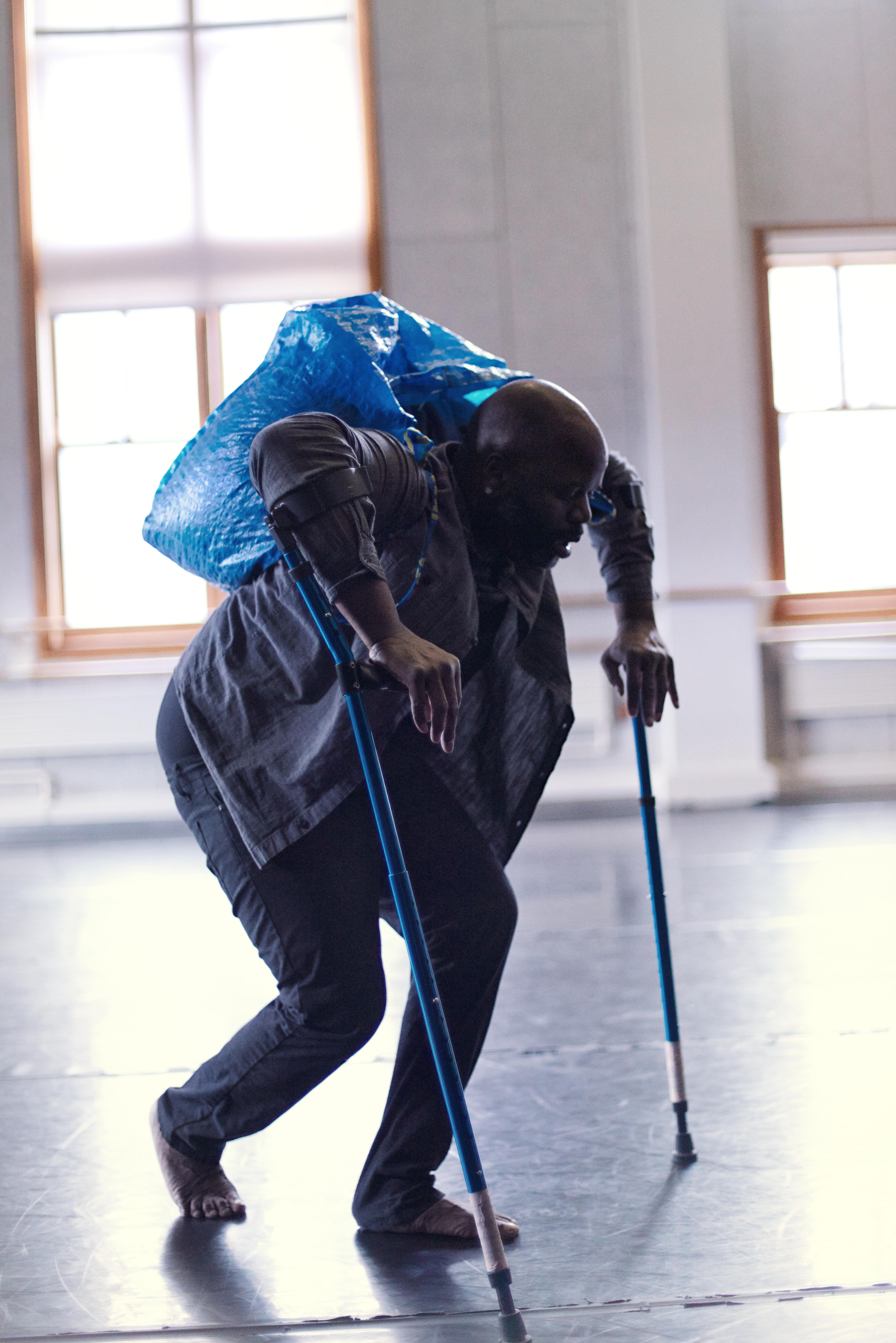 Man in studio dancing while using forearm crutches and wearing a large bag on his back