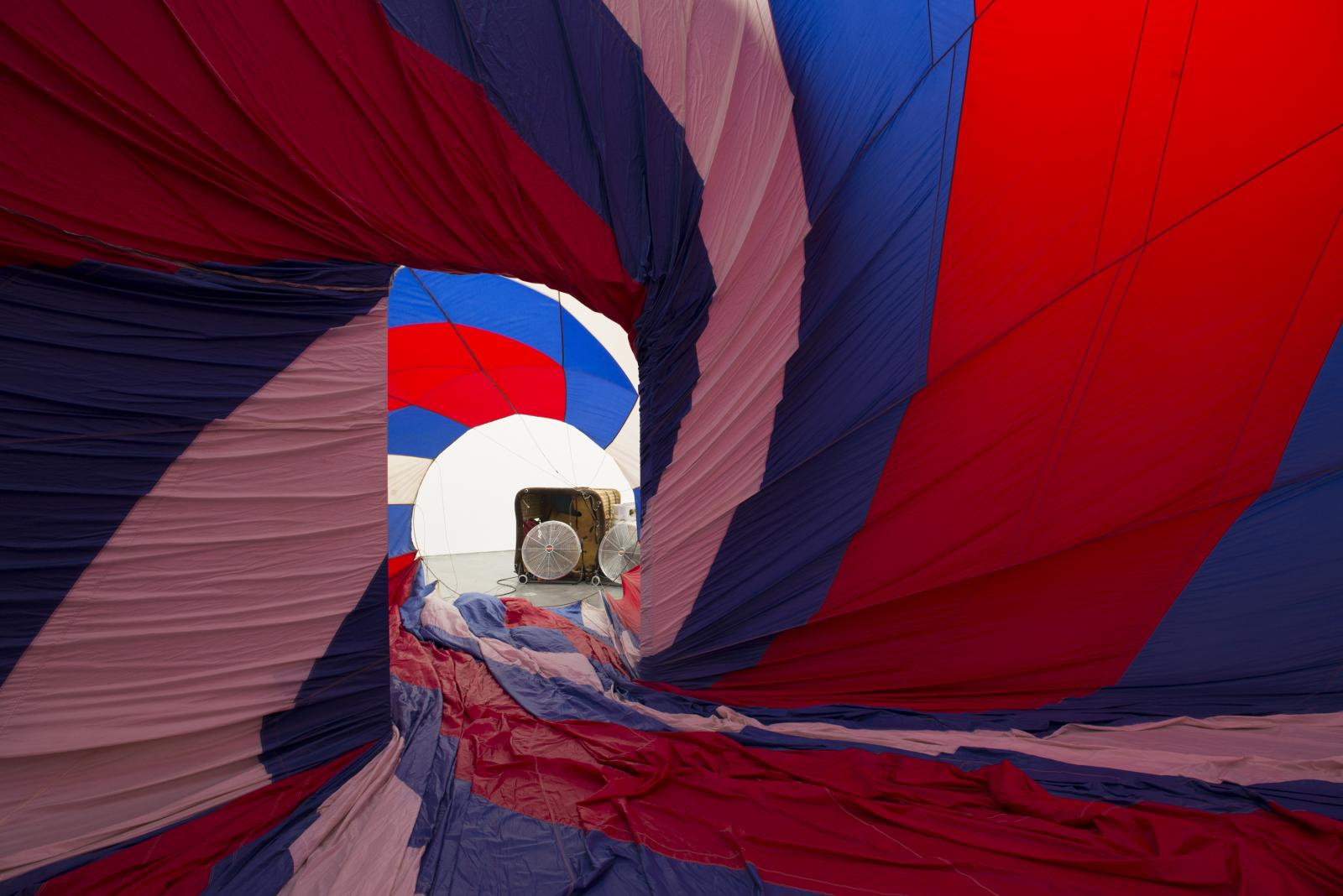 A red, white, and blue fabric canopy presses against walls of room in a spiral; portable fans blow air into the room through a doorway.