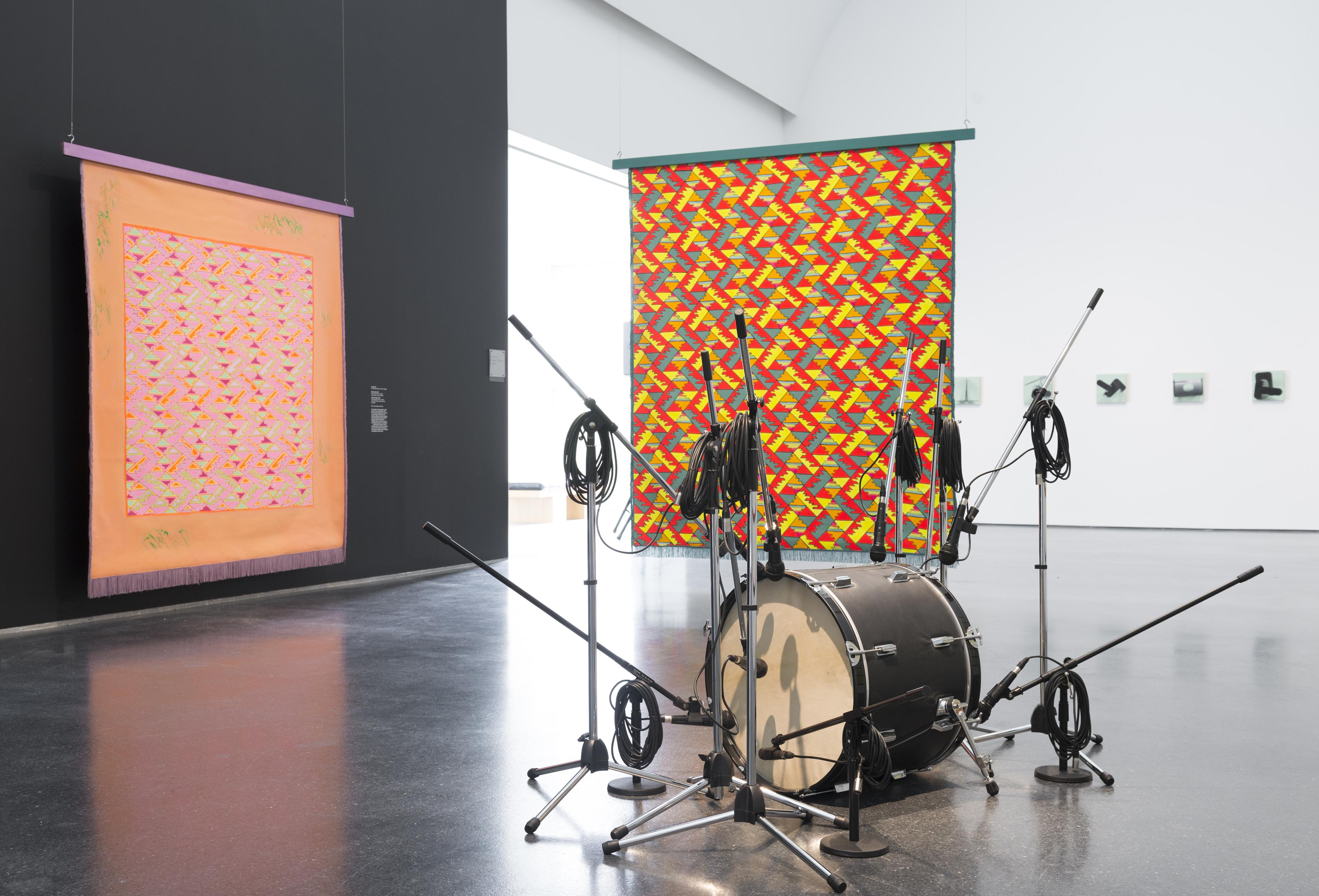 A bass drum surrounded by microphones on stands in front of brightly colored suspended backdrops