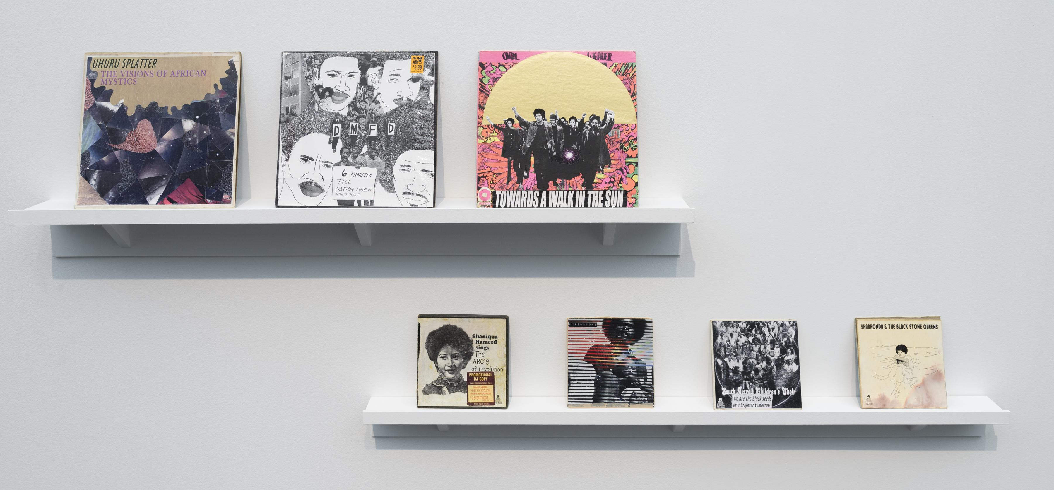 Two wall shelves display a group of illustrated album covers