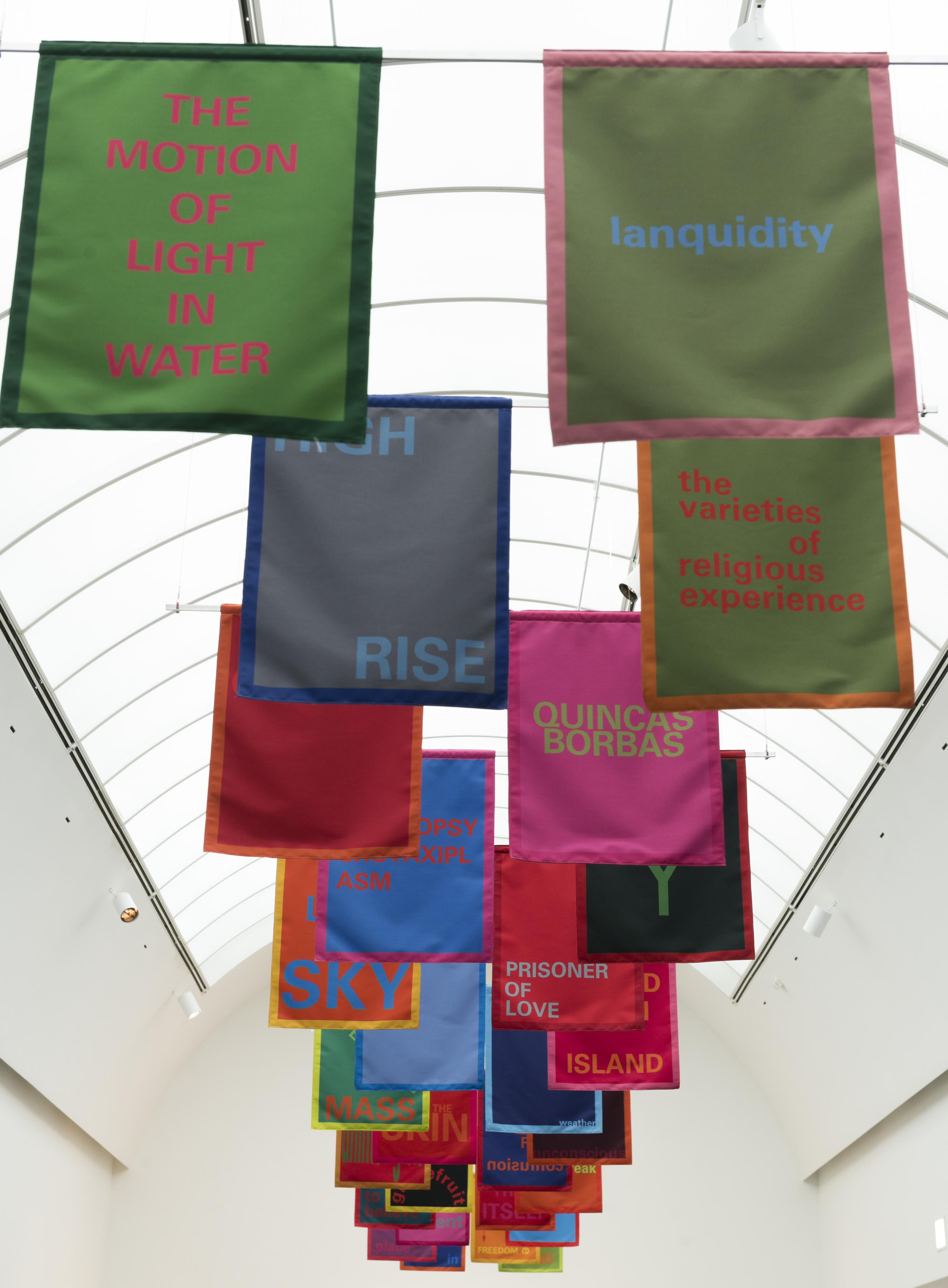 """Colorful banners hang in pairs from the ceiling. Each one features a text, for example, """"THE MOTION OF LIGHT IN WATER,"""" """"lanquidity,"""" """"HIGH RISE,"""" """"the varieties of religious experience."""""""