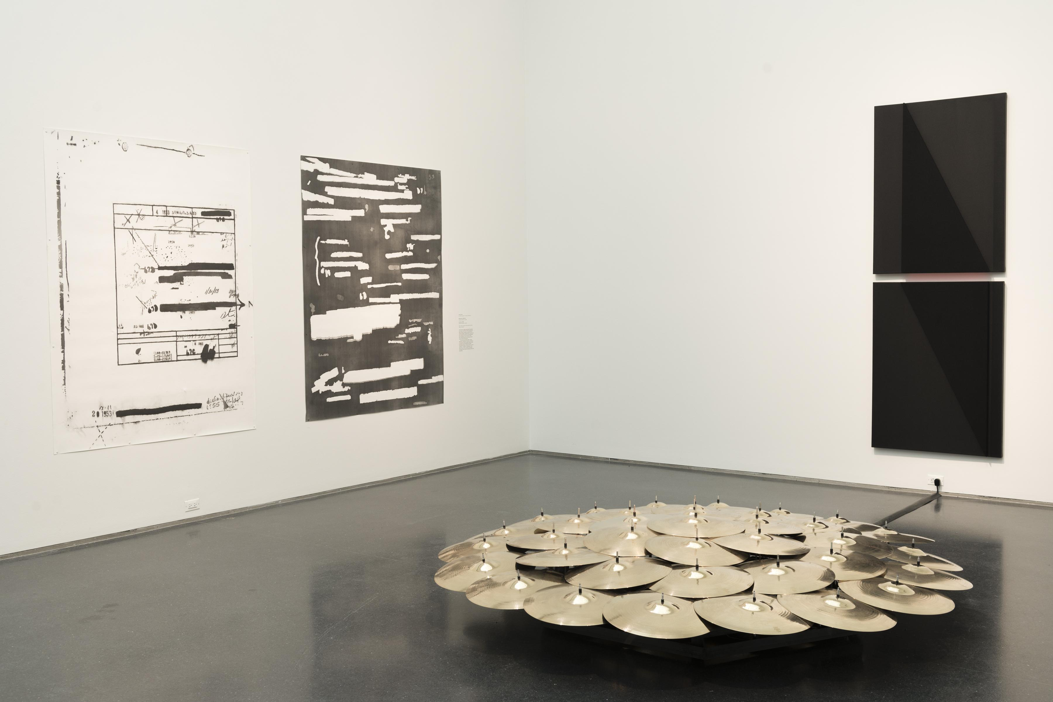 Several dozen brass cymbals are clustered together in a circle. Behind them to the left, two black-and-white paintings hang side by side, and to the right, two black panels are stacked vertically.