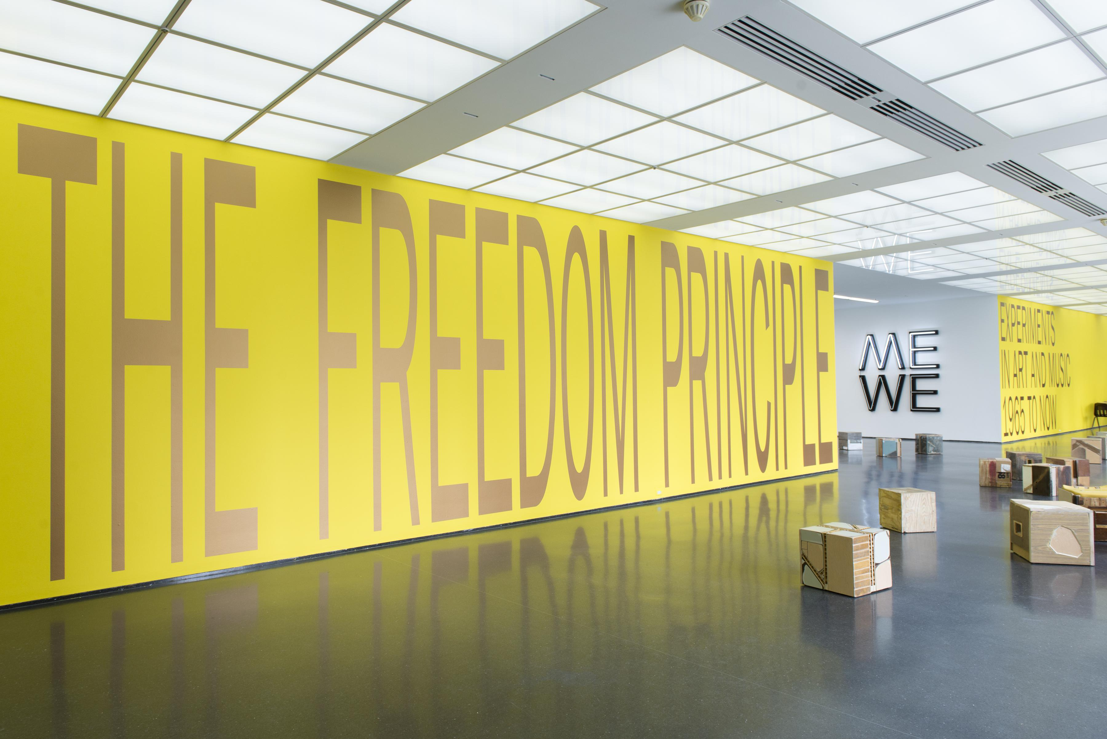"""The bright yellow entry wall of an exhibition bears the floor-to-ceiling title, """"THE FREEDOM PRINCIPLE."""" In the foreground of the image, stool-sized boxes in wood and paper appear; beyond the yellow wall, there is a light installation of the word """"ME"""" stacked atop the word """"WE."""""""