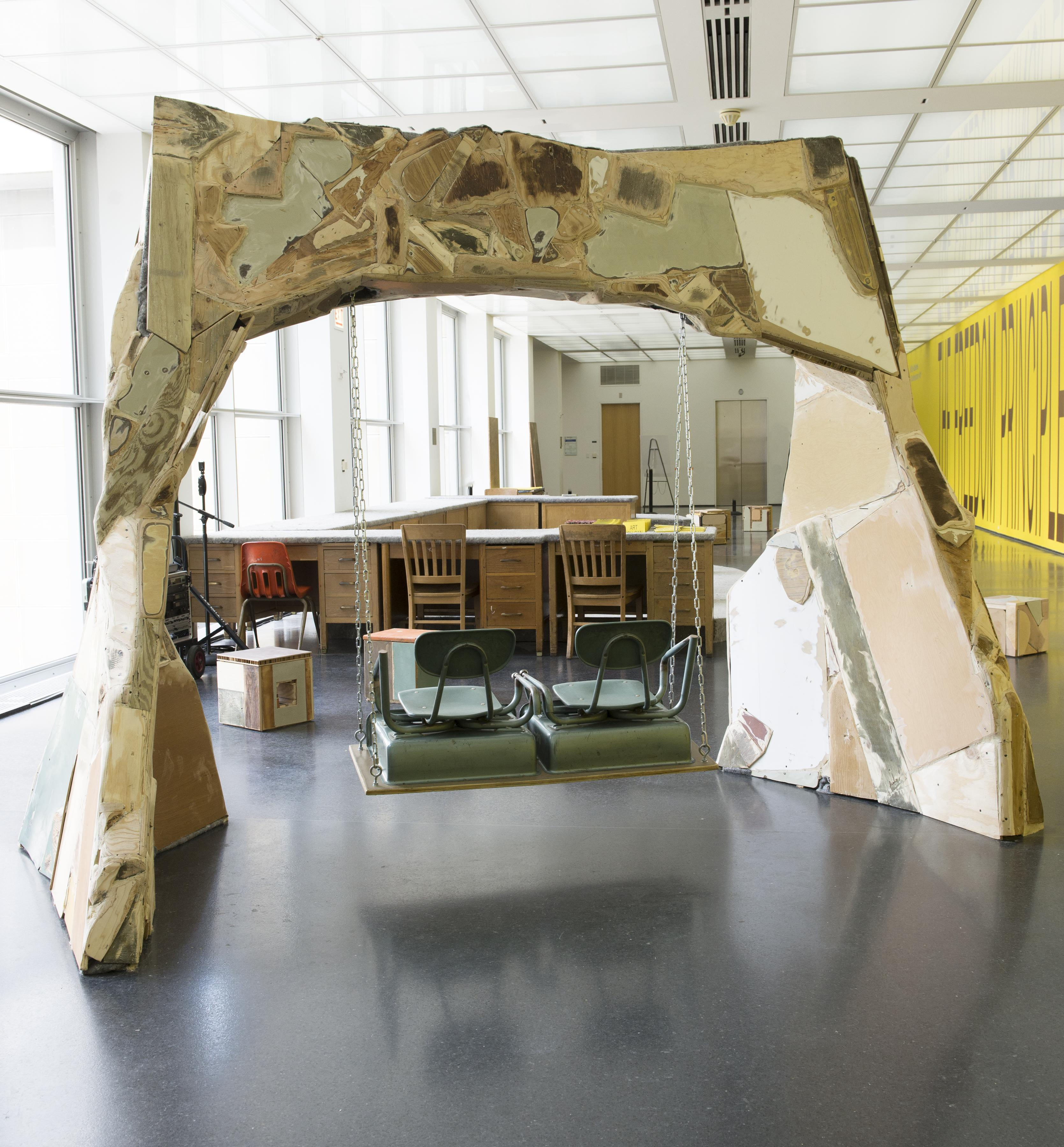 A two-seat swing made of school chairs hangs from an arch constructed from found materials crudely patched together.