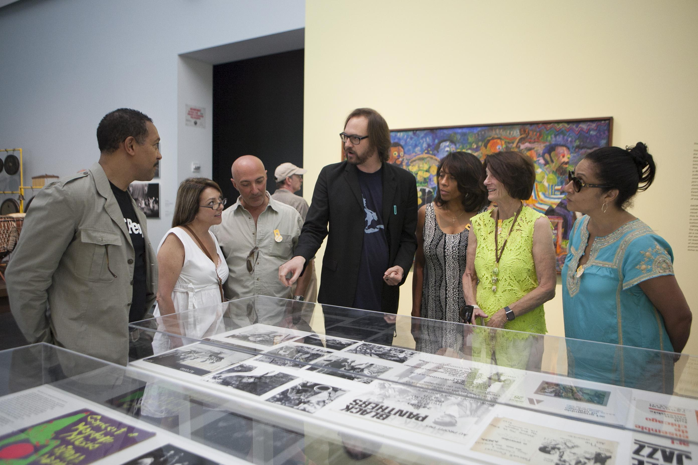 The exhibition curator speaks with a small group inside *The Freedom Principle* exhibition.