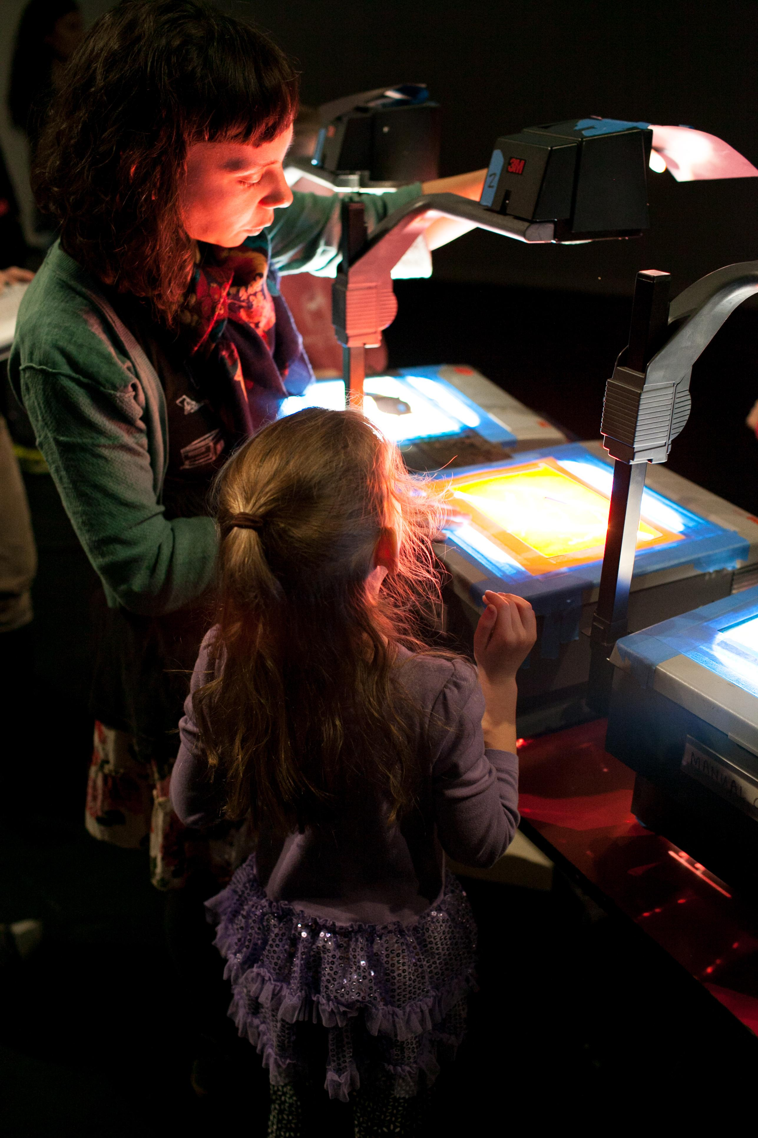 A woman and girl position a transparency on an overhead projector.