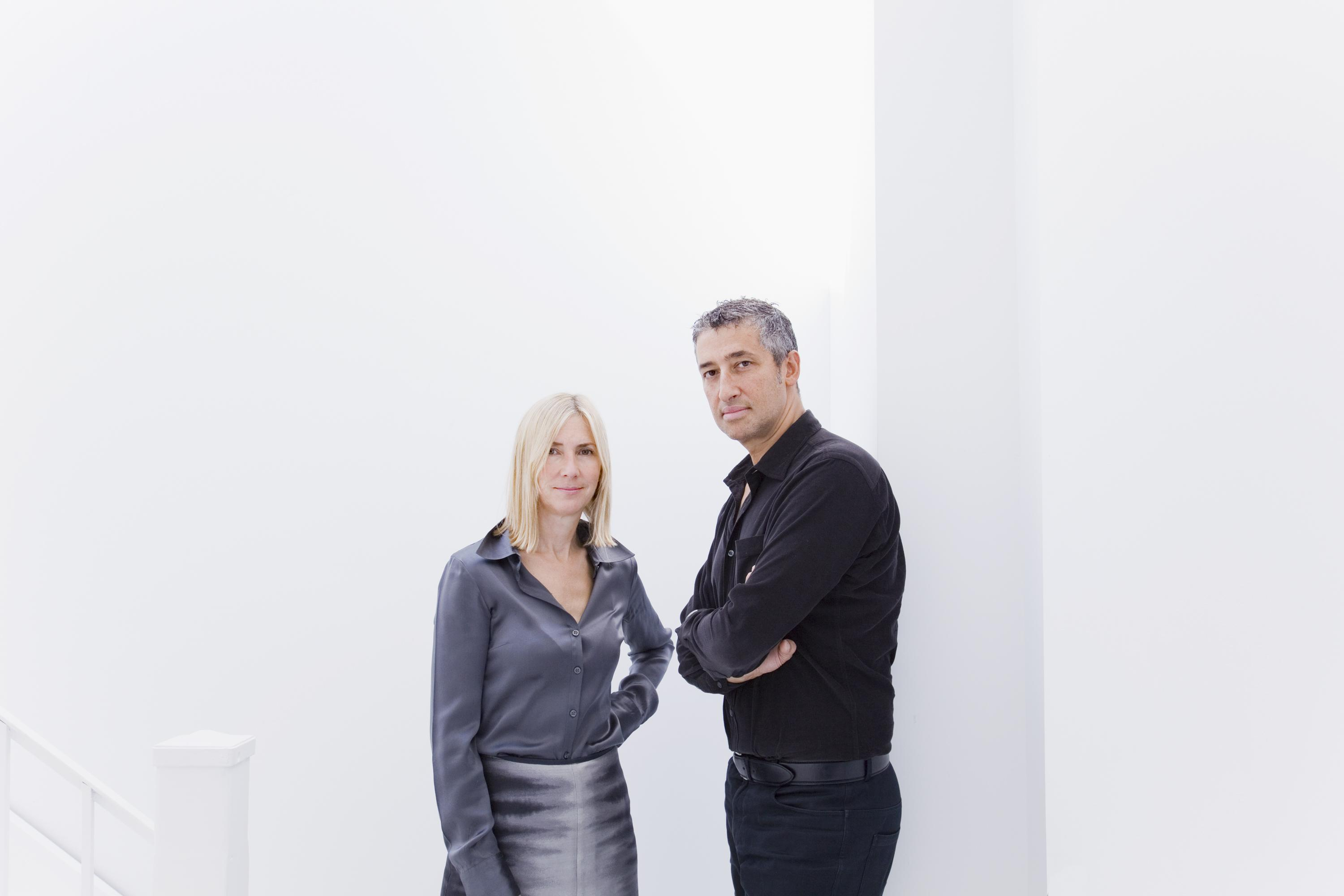 A woman and man in business casual clothing pose in front of a white wall