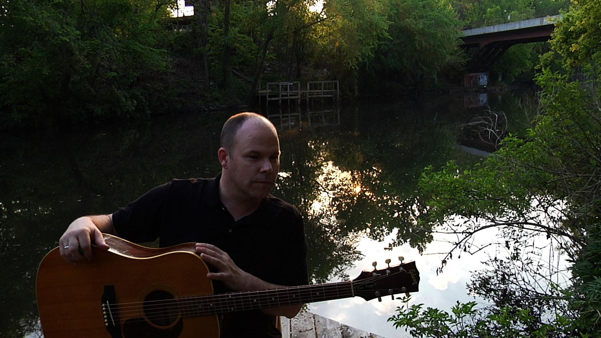 A man holding a guitar in front of a secluded tree-lined body of water