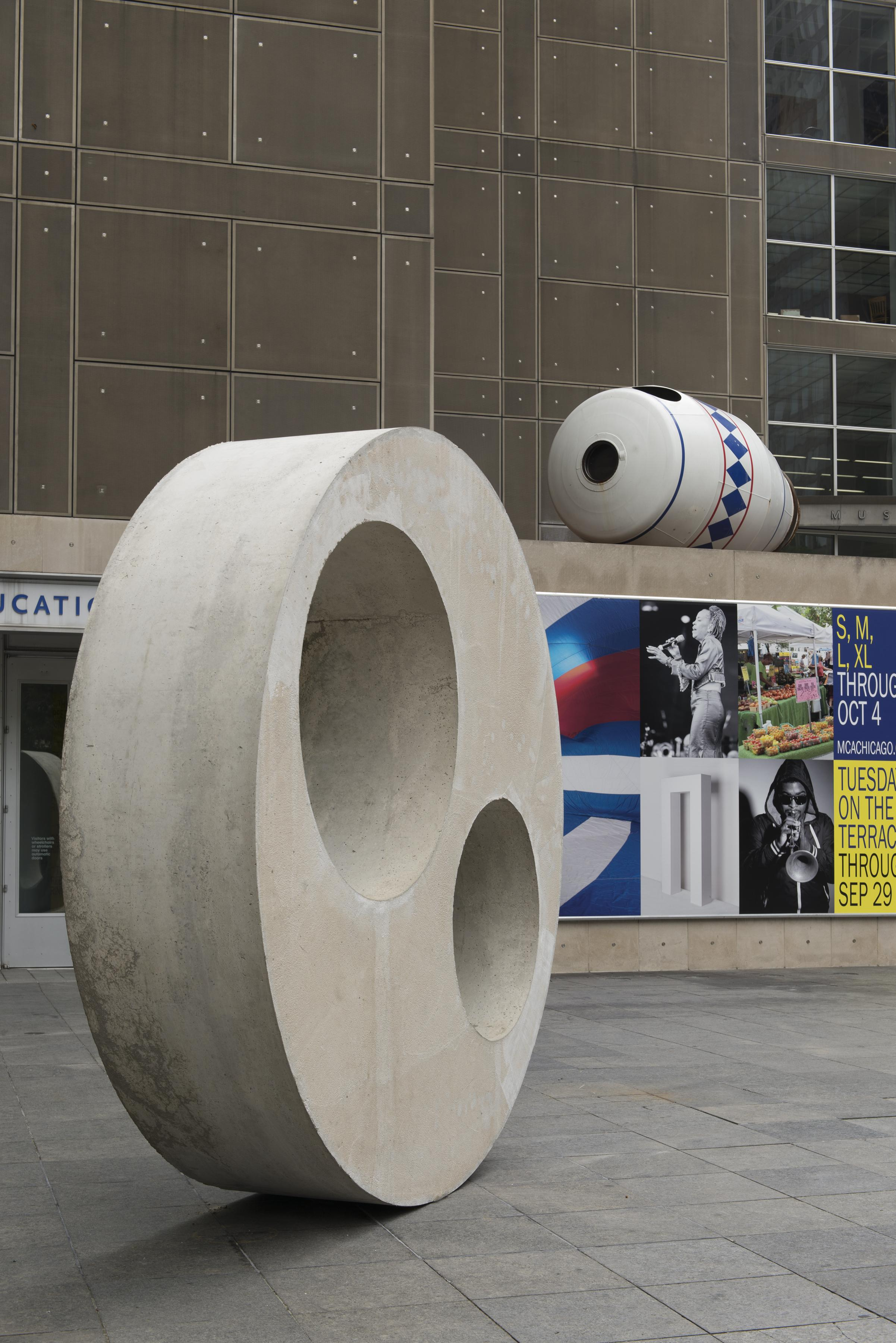 Close-up of a large concrete disc and a white container-shaped sculpture on the MCA Plaza