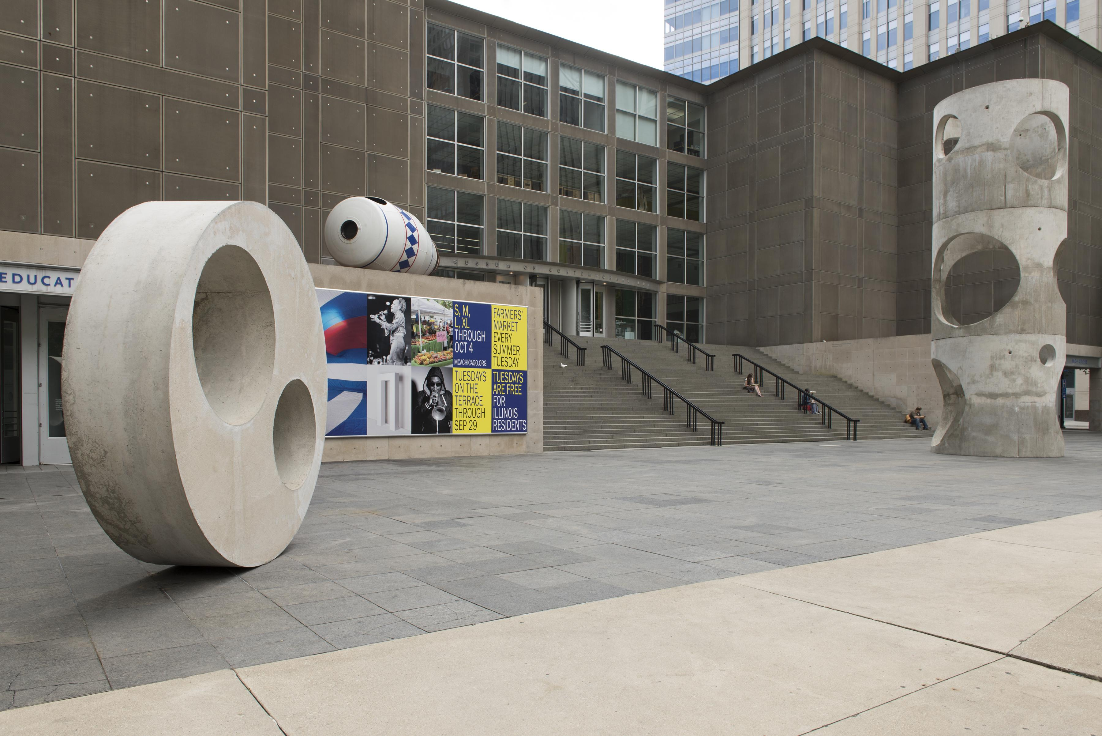 Two large concrete sculptures and a large white container-shaped sculpture on the MCA Plaza