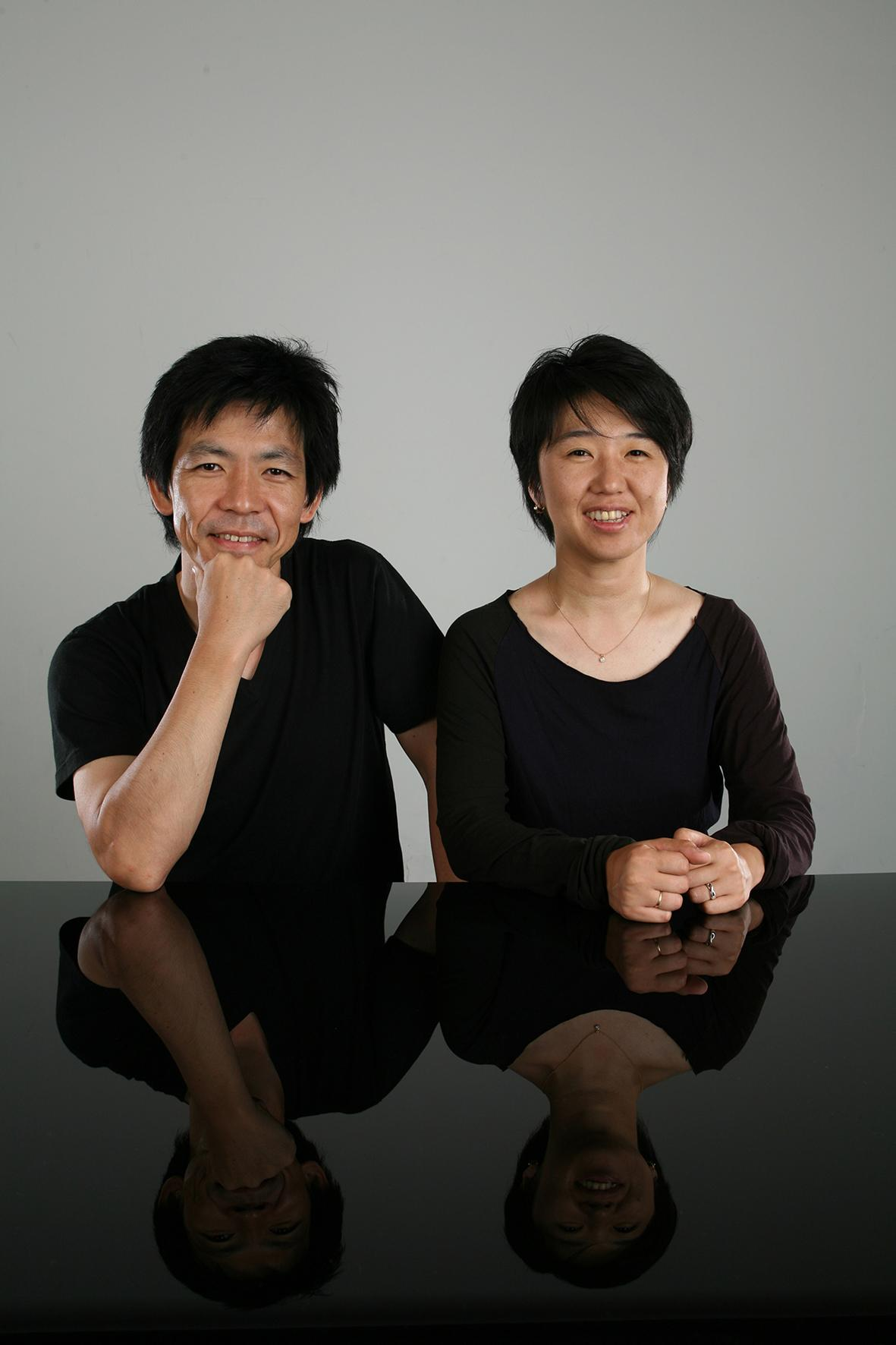 A portrait shows a man and woman wearing black and resting their arms on a glossy black tabletop in front of them.