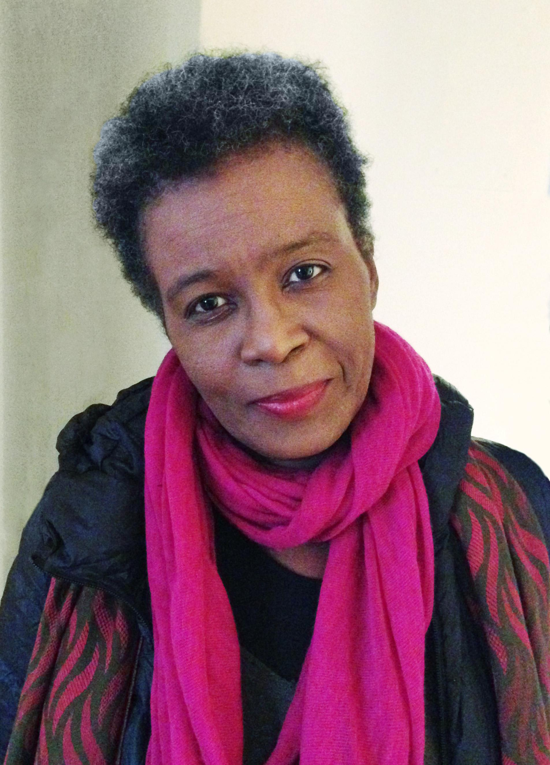 A photographic portrait shows a middle-aged, dark-skinned woman cocking her head and wearing a bright pink scarf.