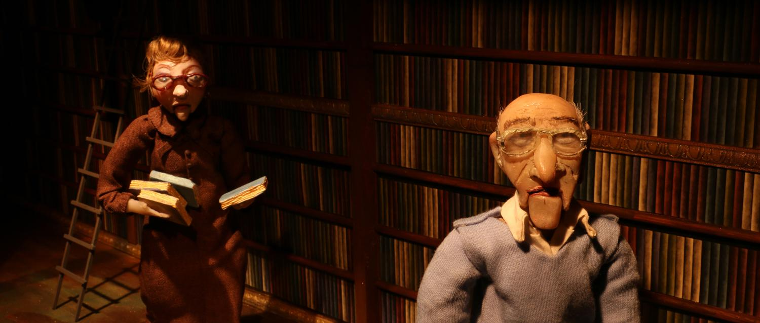 Puppets of an old man and woman walk through a dark room past a wall lined with books.