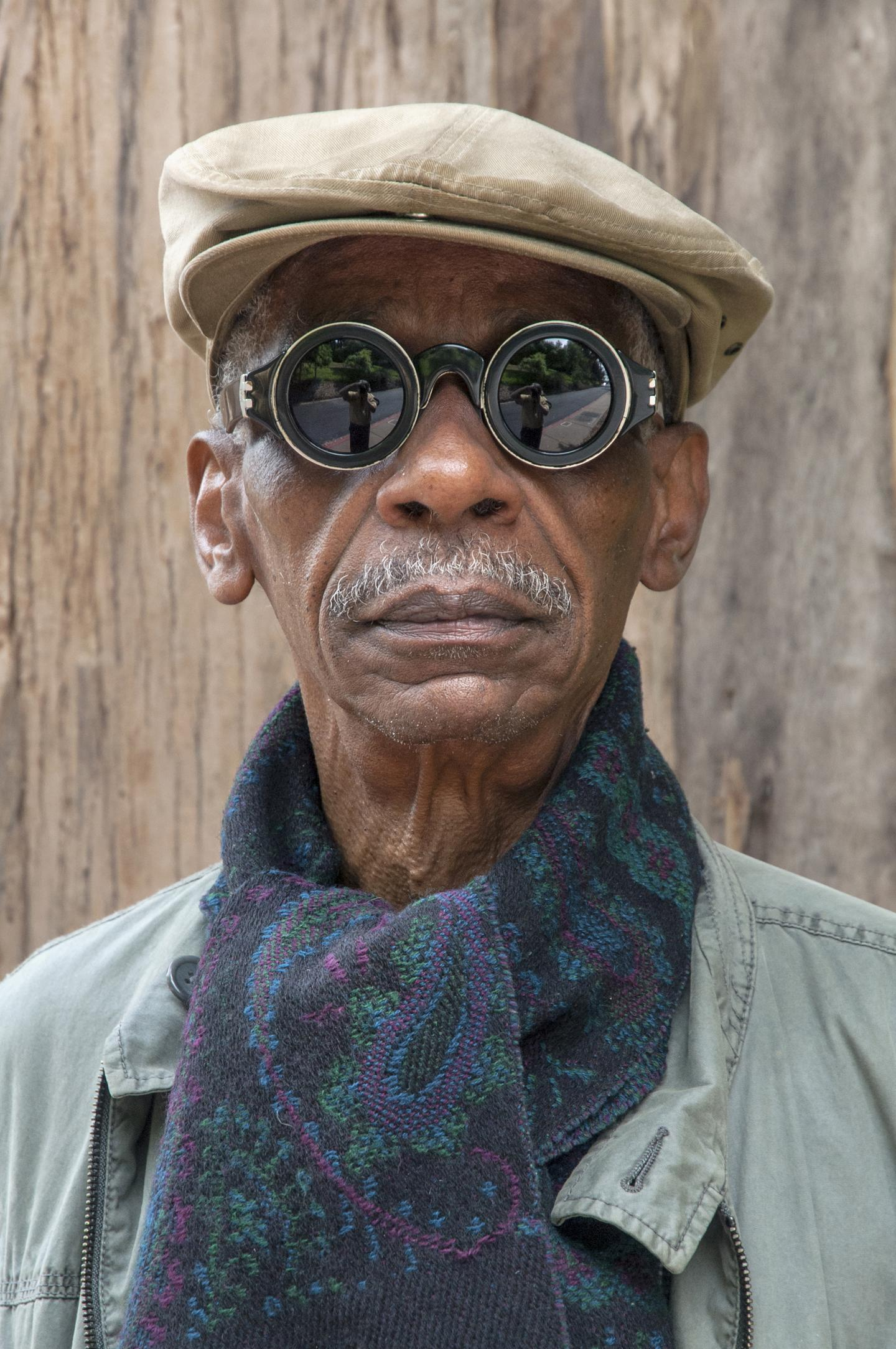 A photographic portrait shows a dark-skinned older man wearing circular mirrored sunglasses, a khaki flat cap, and a multicolored scarf.
