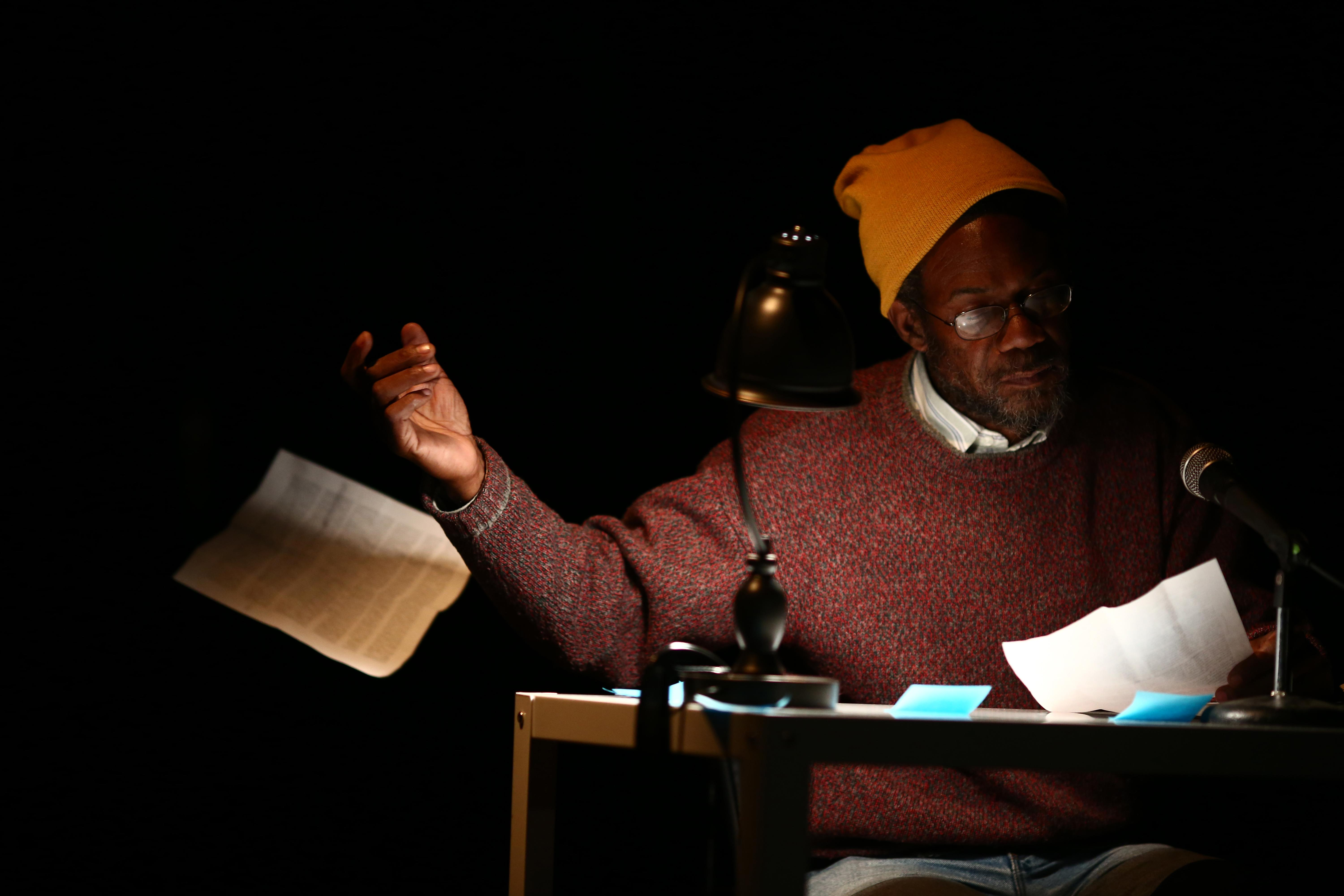 A dark-skinned older man sits at a table illuminated by a desk lamp on an otherwise pitch-black stage. He looks at one sheet of paper and tosses another to the floor.