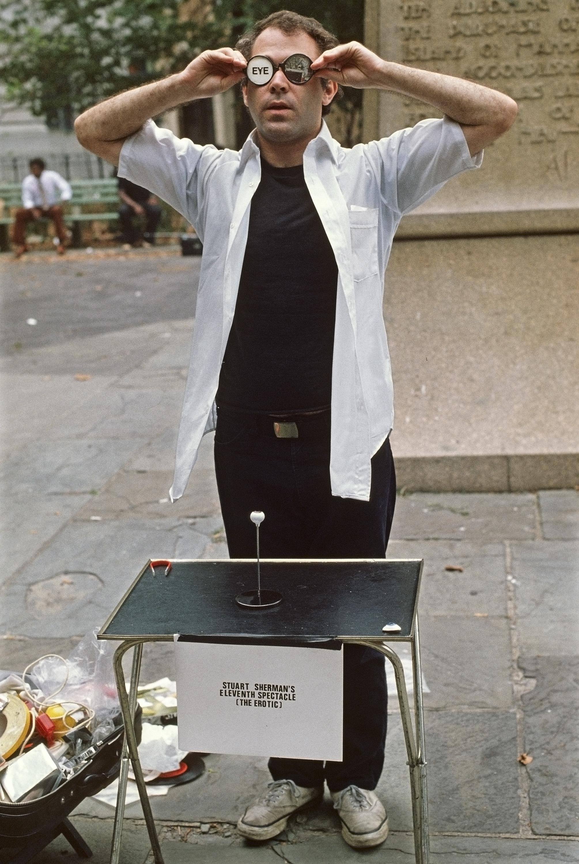 A performance still shows a man in a public park putting on round glasses that contain pieces of paper in place of lenses.