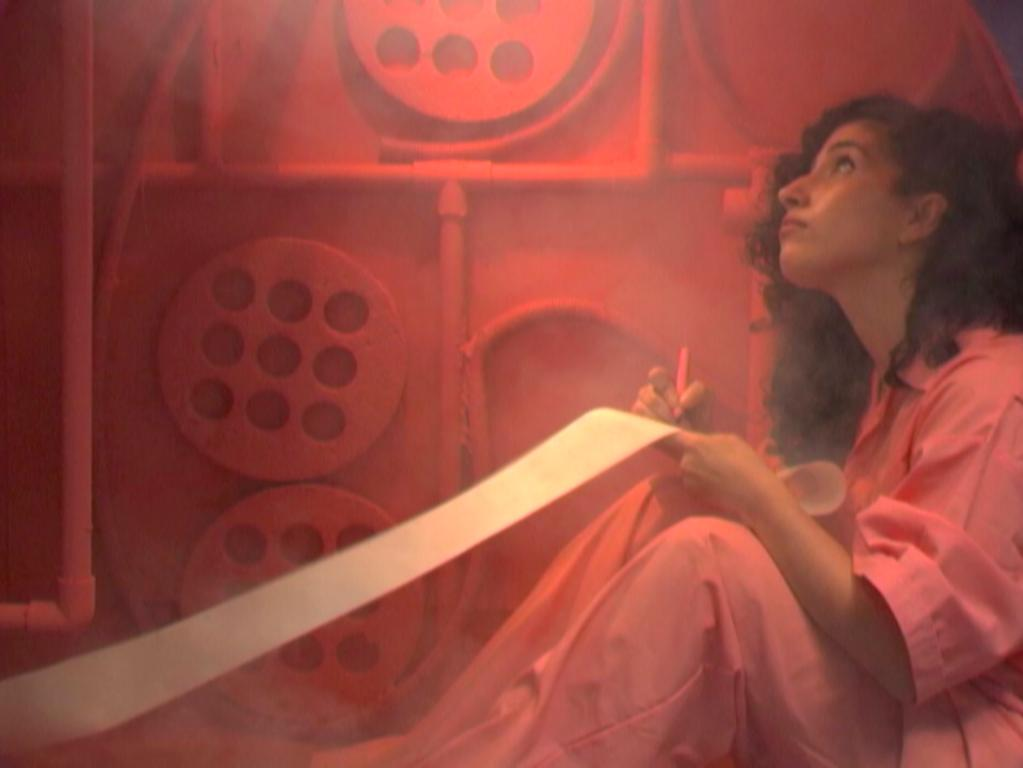 A film still shows a woman sitting on the floor, dressed in the same pink color as the wall behind her and writing on a long sheet of paper