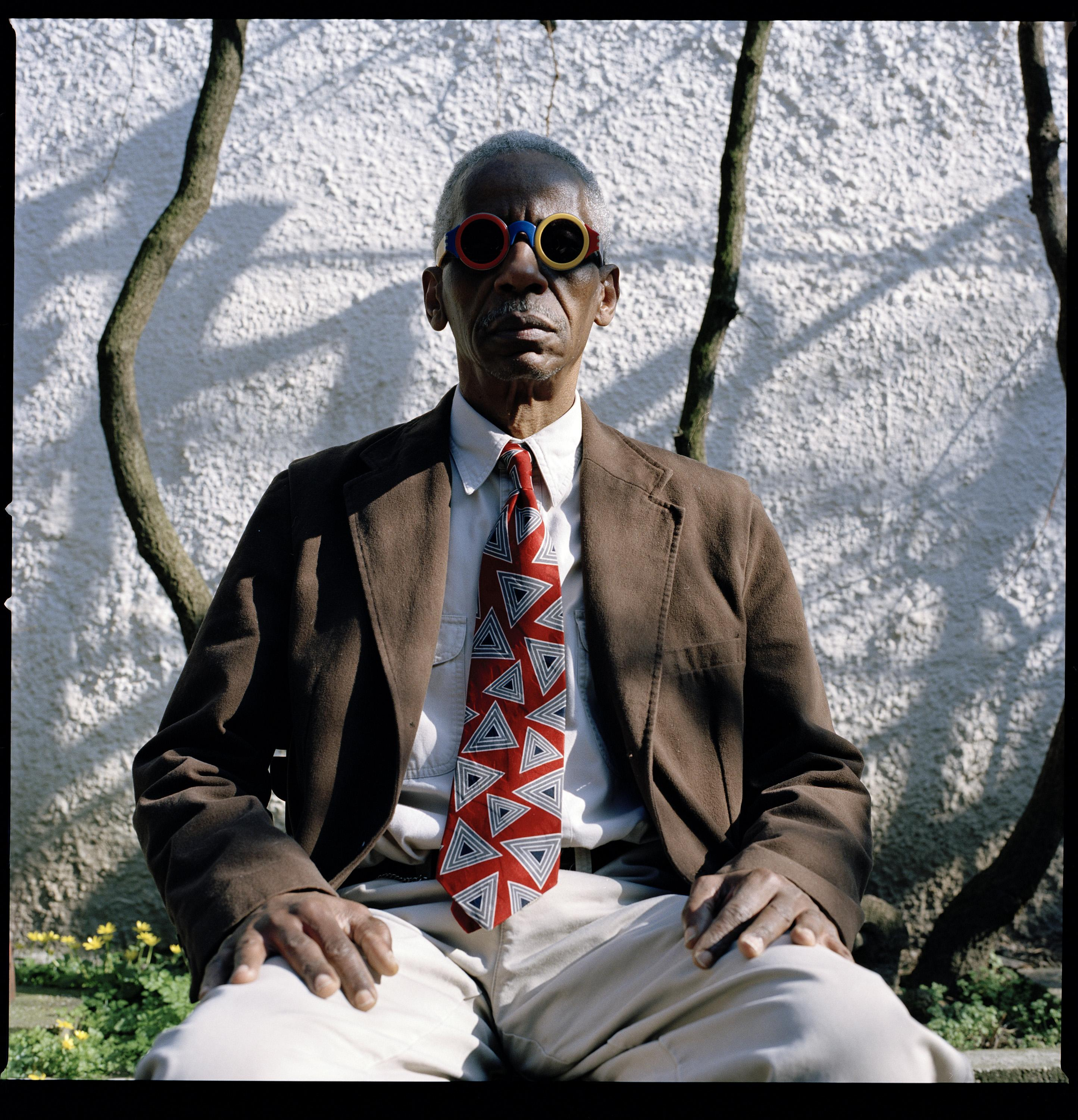 A photographic portrait shows a seated, dark-skinned man wearing a brown jacket, colorful sunglasses, and a boldly patterned tie.