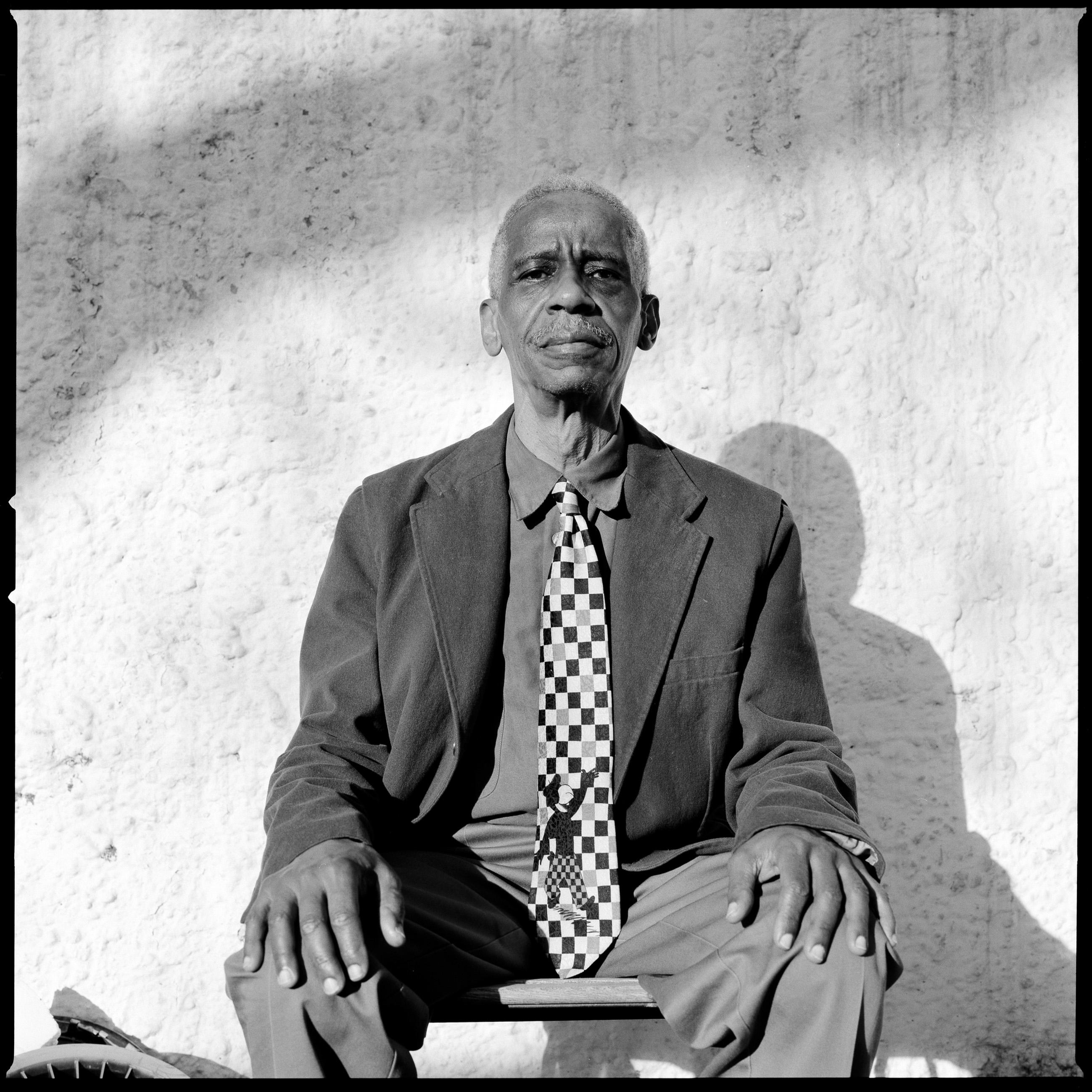 A black-and-white portrait of Roscoe Mitchell sitting on a chair.