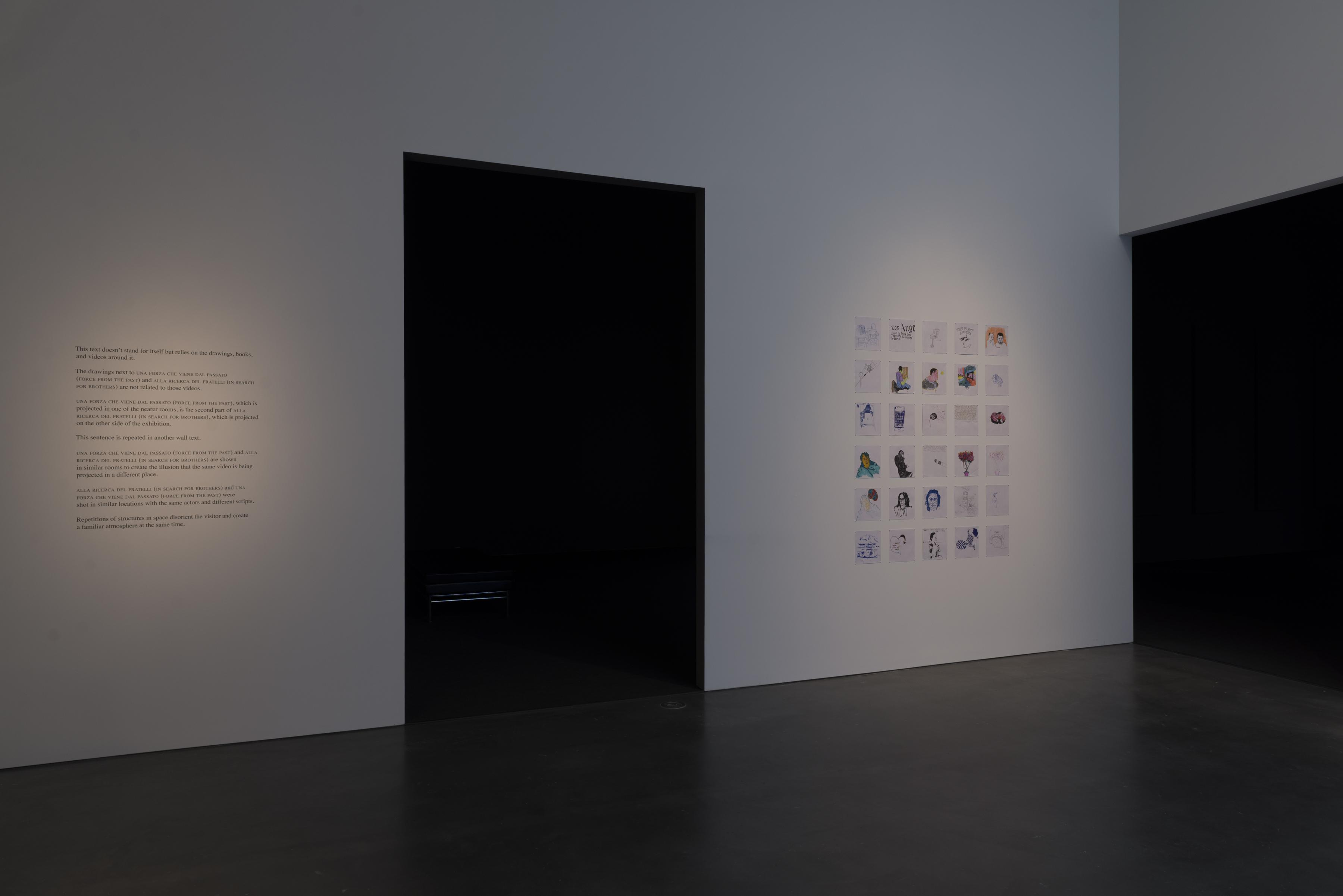 A four-by-six grid of square drawings on a wall between two large black doorways