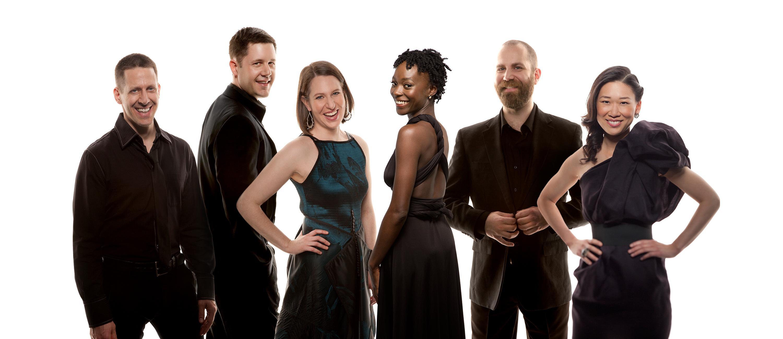 Six smiling people sport dark-colored formal wear