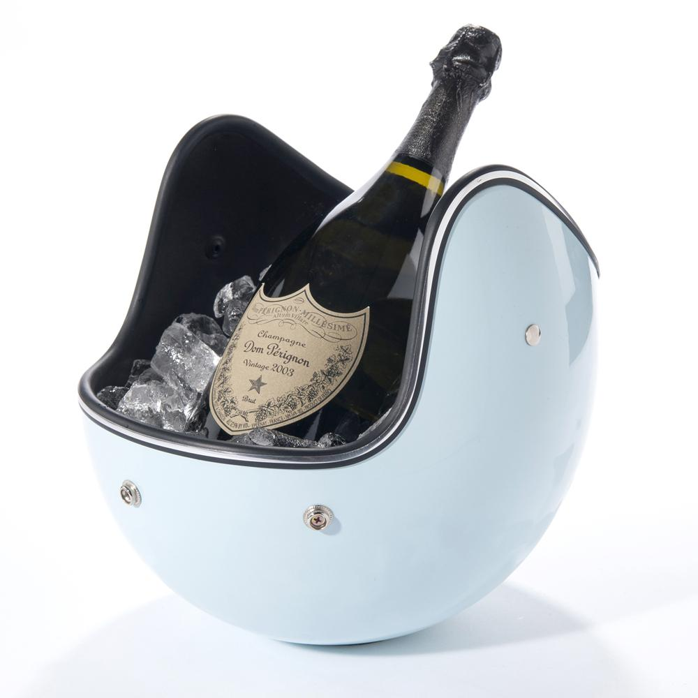 A light-blue motorcycle helmet balances upside-down, filled with ice and a bottle of champagne.