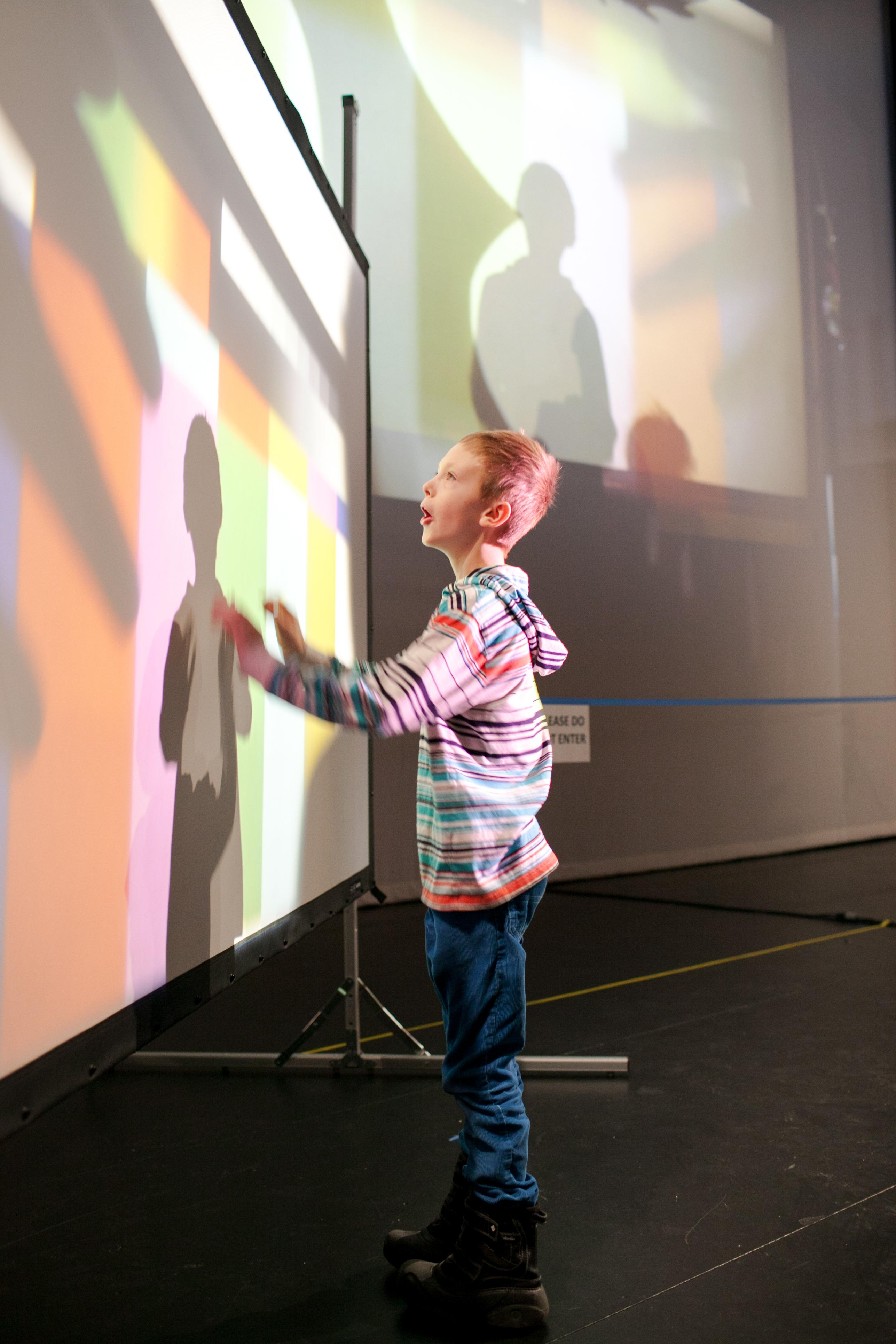 A young boy reaches out to touch a screen projected with a grid of colorful rectangles.
