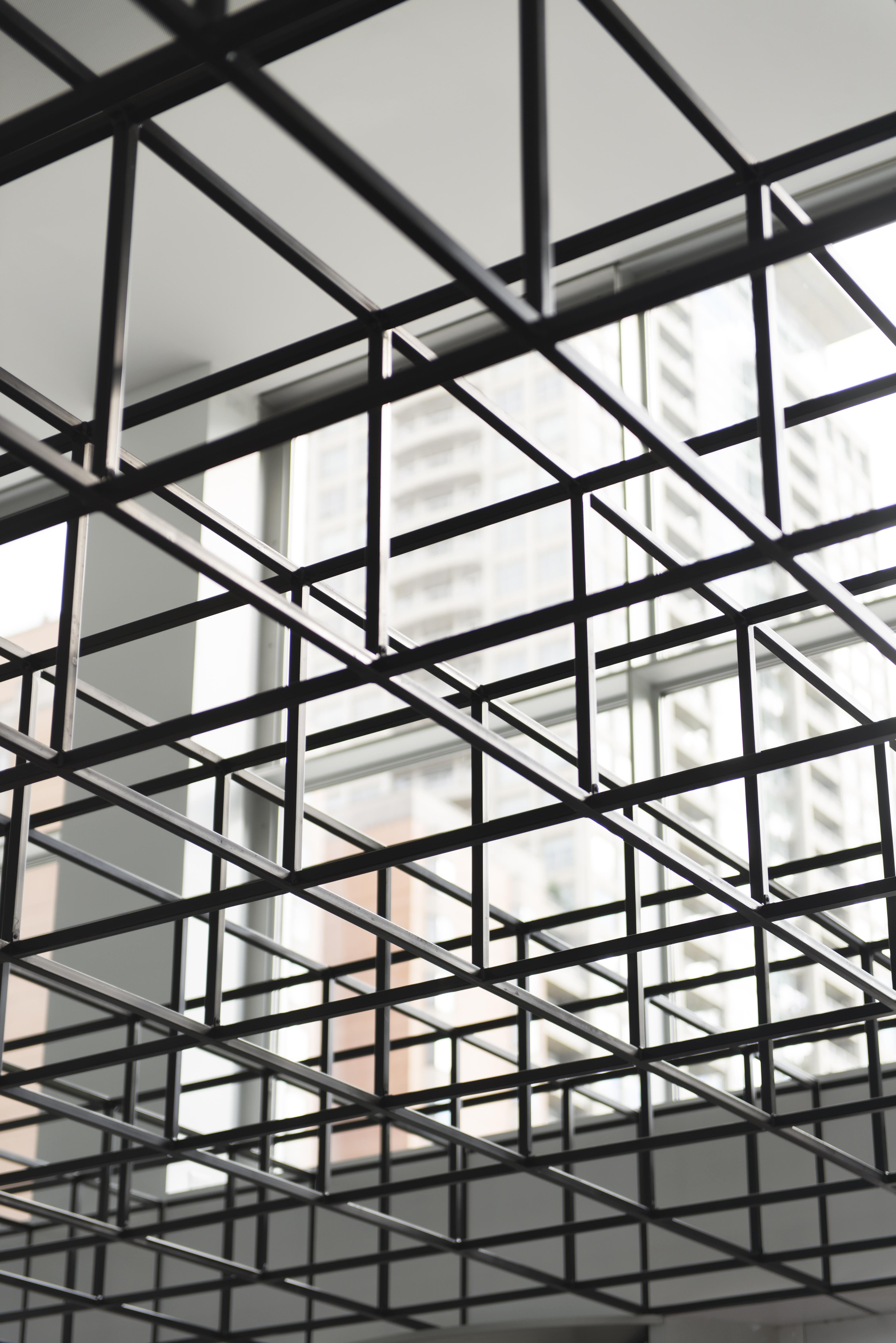 A grid of black, open-sided cubes photographed from below with a large window in the background