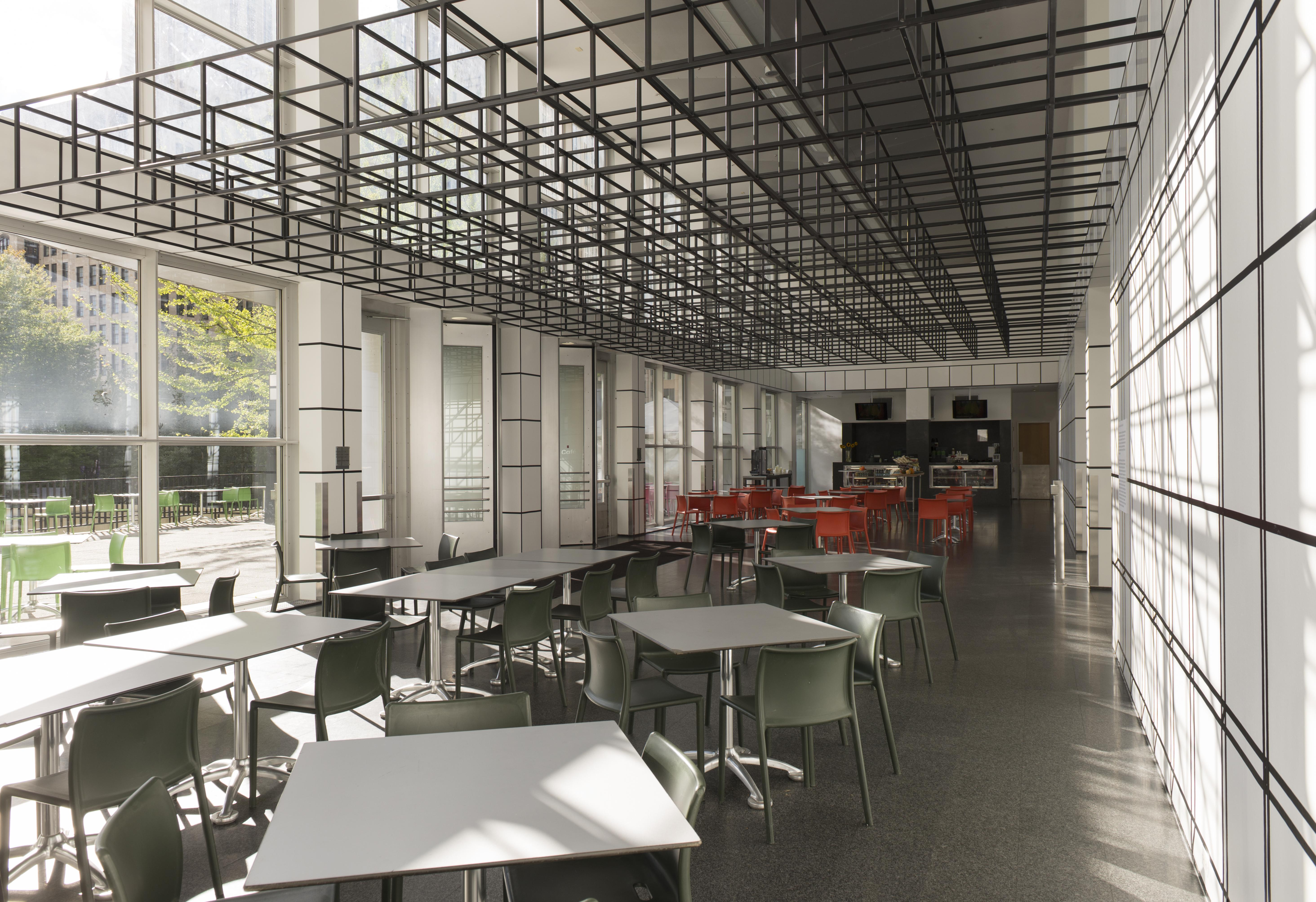 The MCA Cafe with chairs, tables, and a ceiling plane made of open-sided cubes that transitions into grids of illusionistic cubes on the walls
