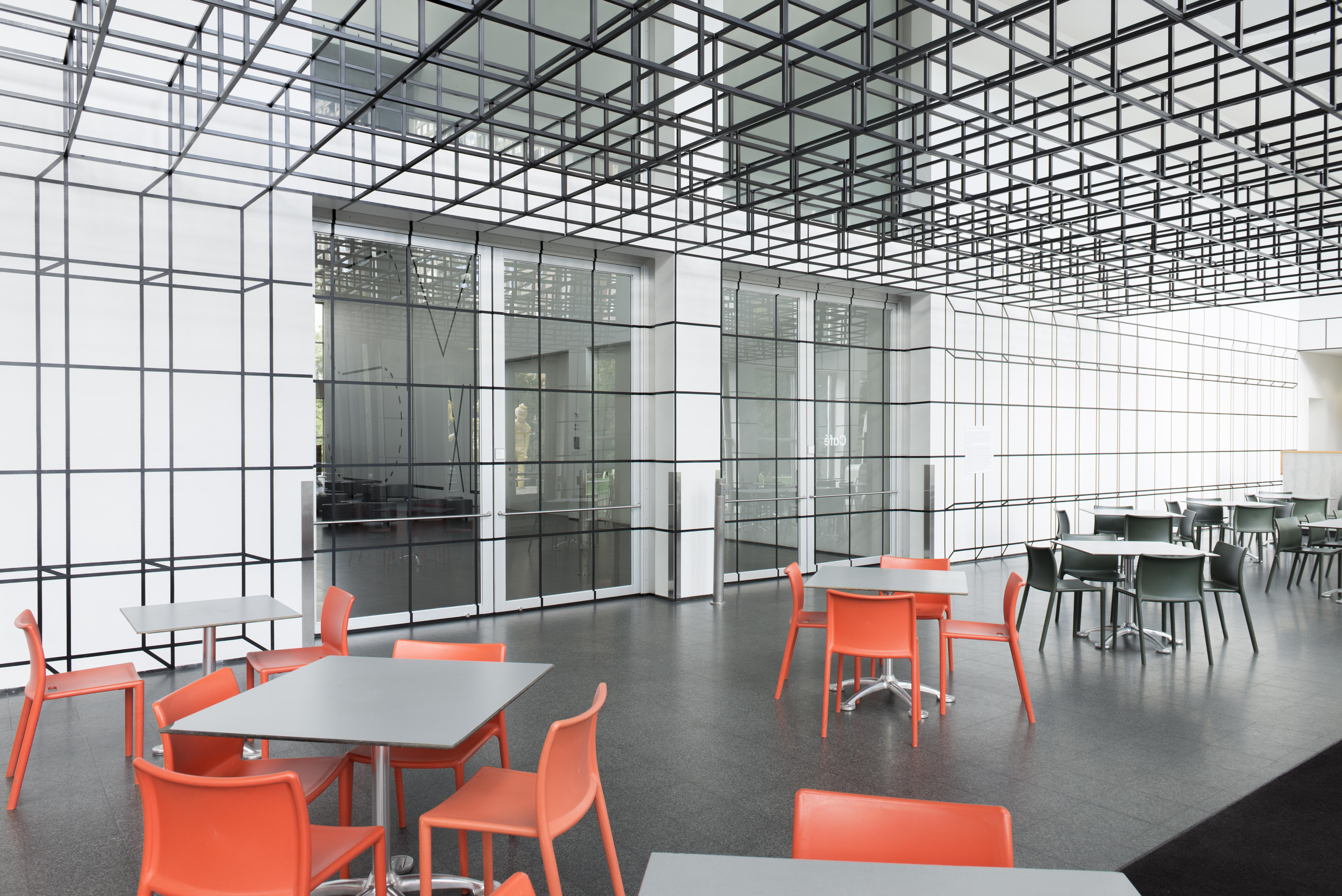 MCA Cafe with chairs and tables and a ceiling plane made of grey, open-sided cubes that semlessly transitions into a grid of illusionistic cubes on the wall