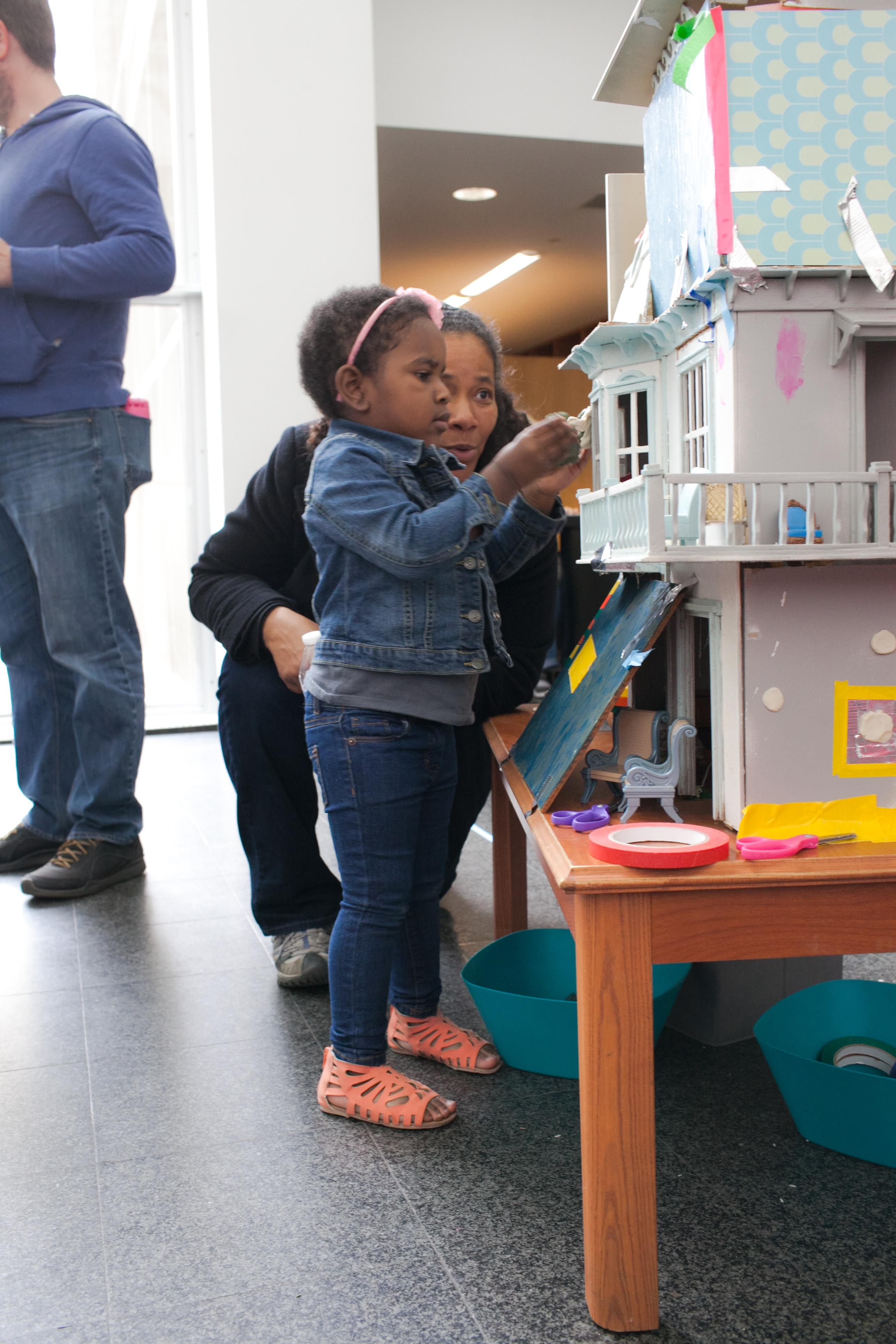 A woman crouches next to a young girl playing with a large doll house in the MCA's atrium.