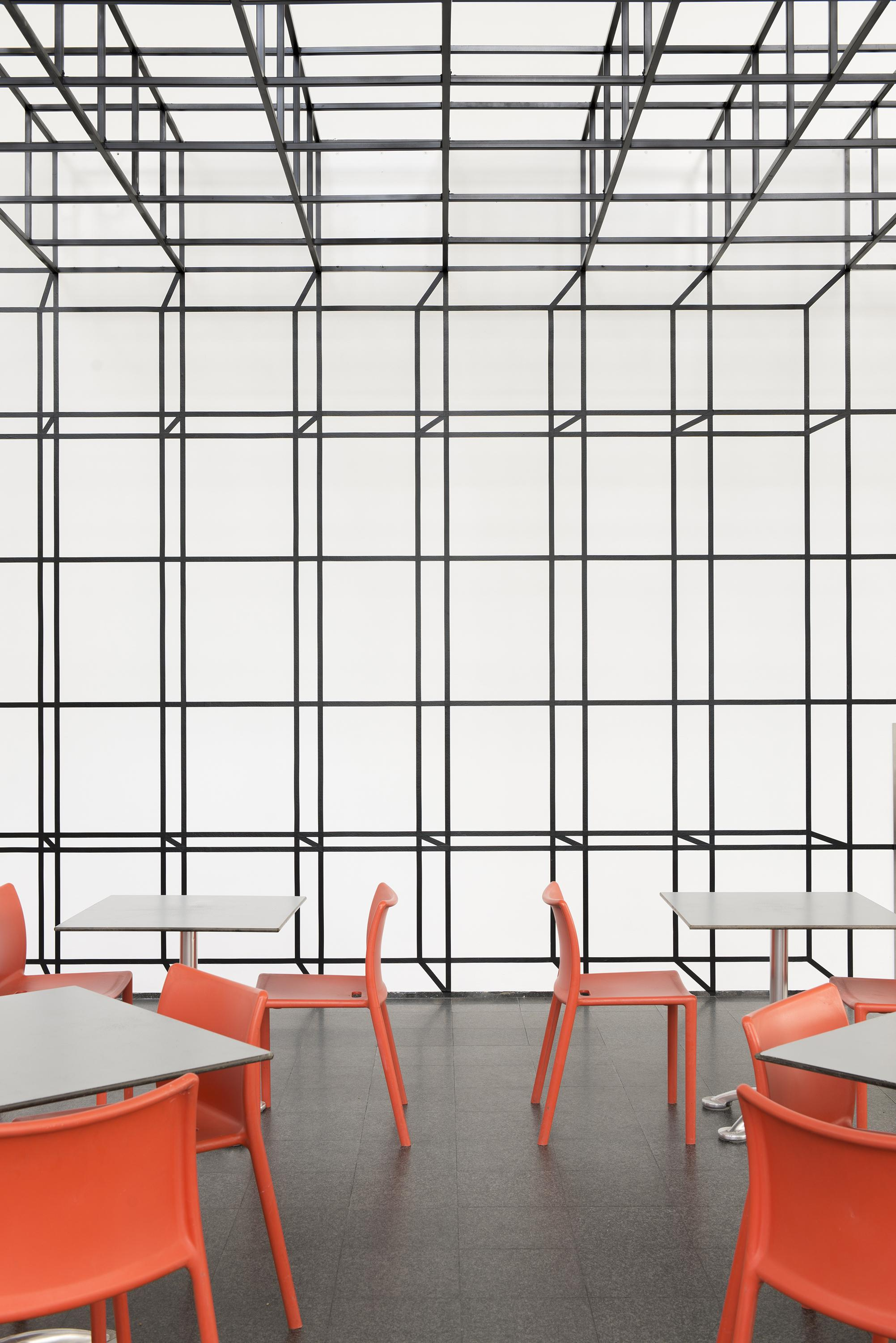 A room with orange chairs and white tables and a ceiling plane made of gray, open-sided cubes that seamlessly transitions into a grid of illusionistic cubes on the wall