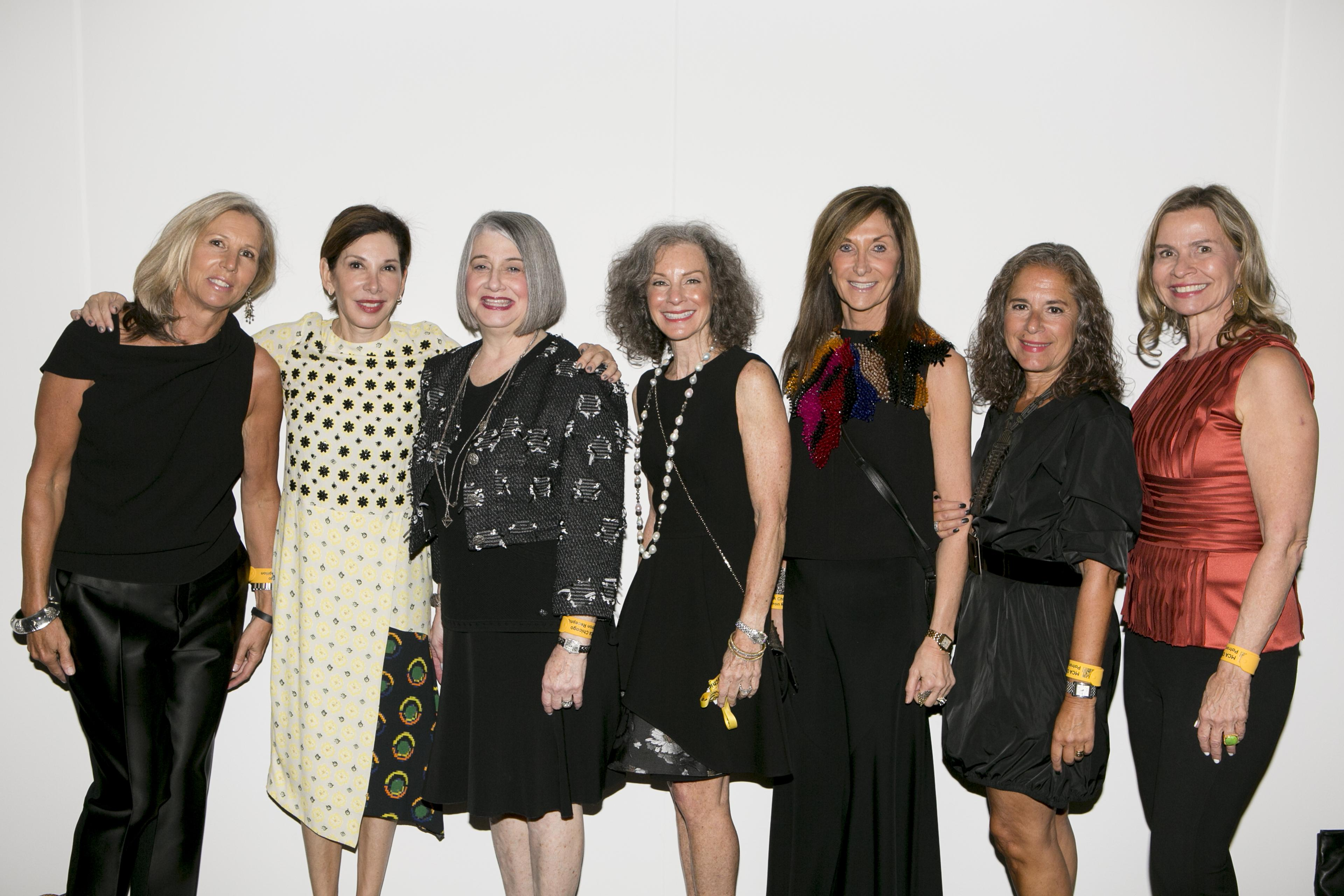 Seven women in cocktail attire pose in front of a white wall.