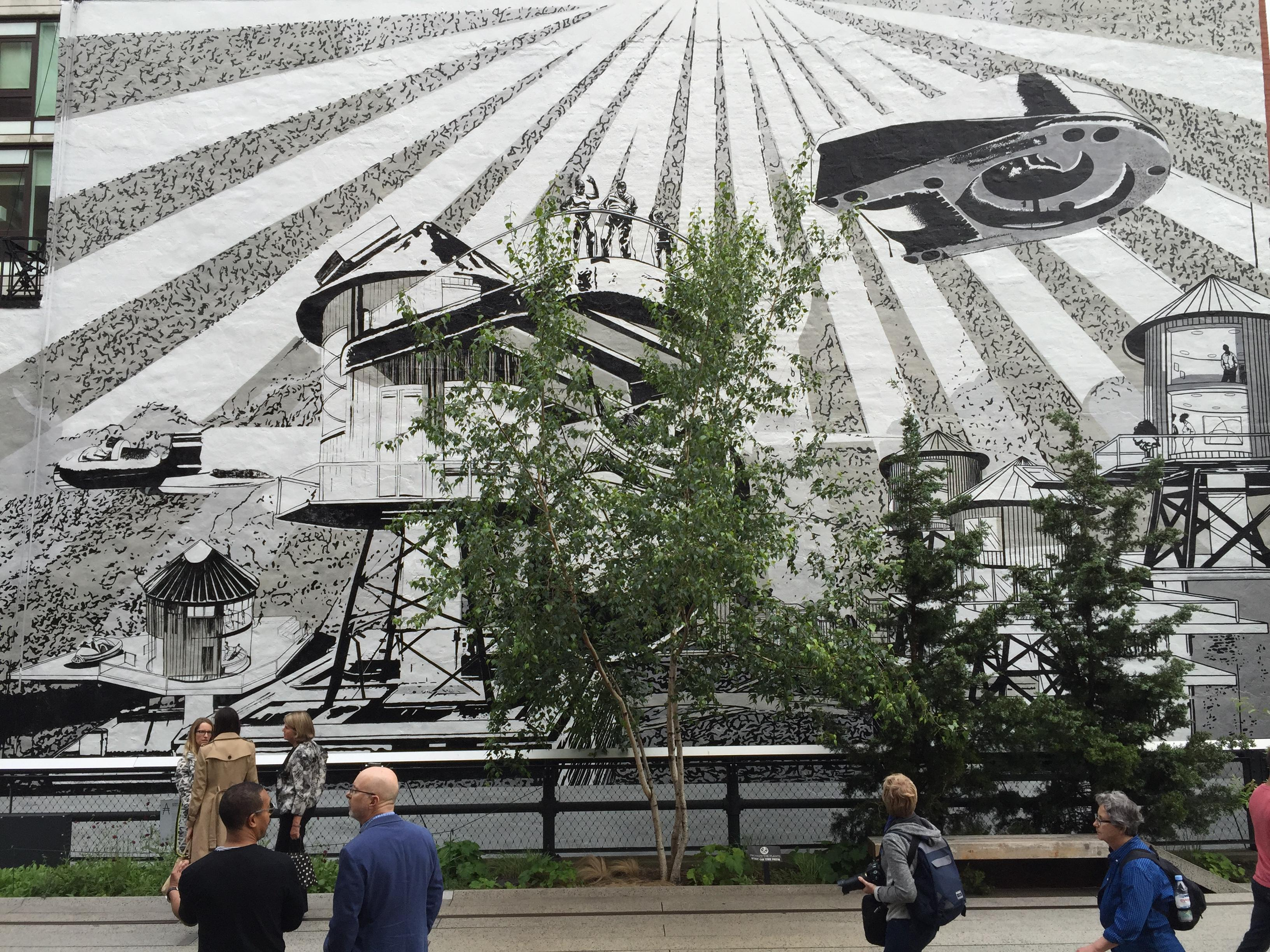 People in a park pass by a large black-and-white mural whose illustrations blend classic urban structures with sci-fi elements.
