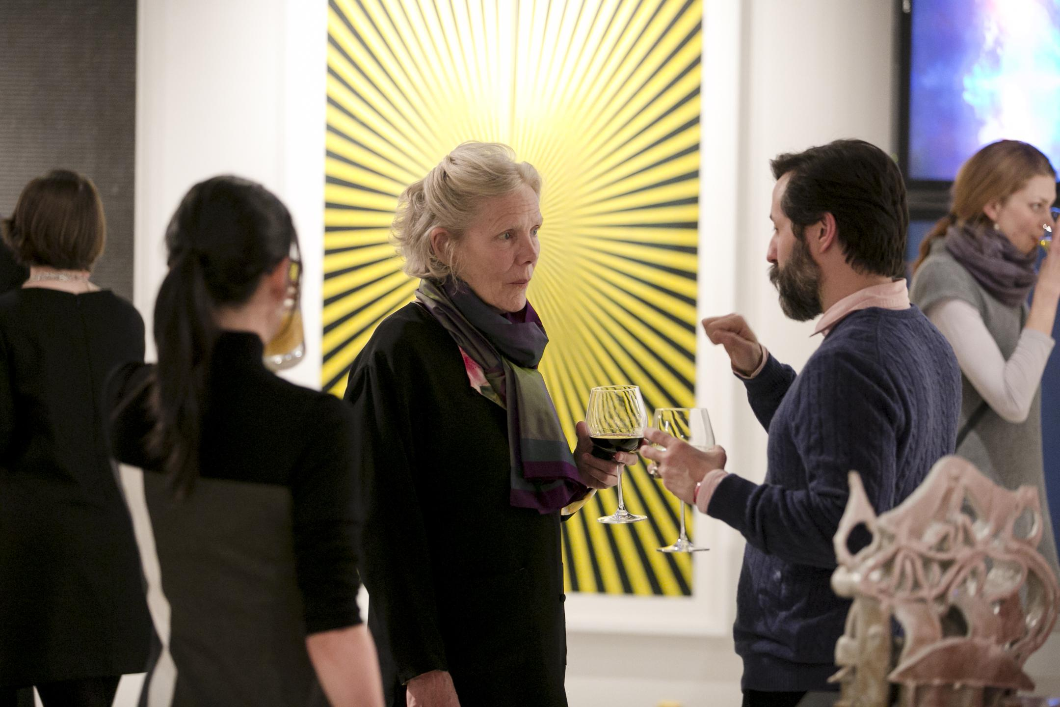 A trio of people socialize and drink wine in a gallery.