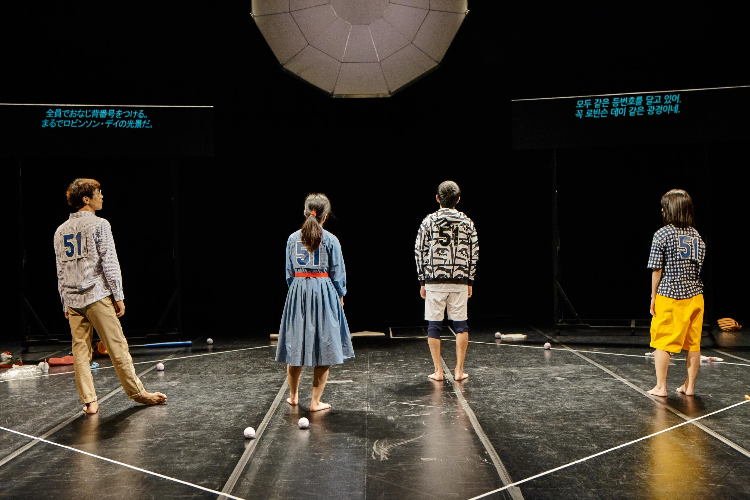 A performance still shows four people wearing the number 51, facing the back of the dark stage, and standing inside the white outline of a square with a few baseballs at their feet