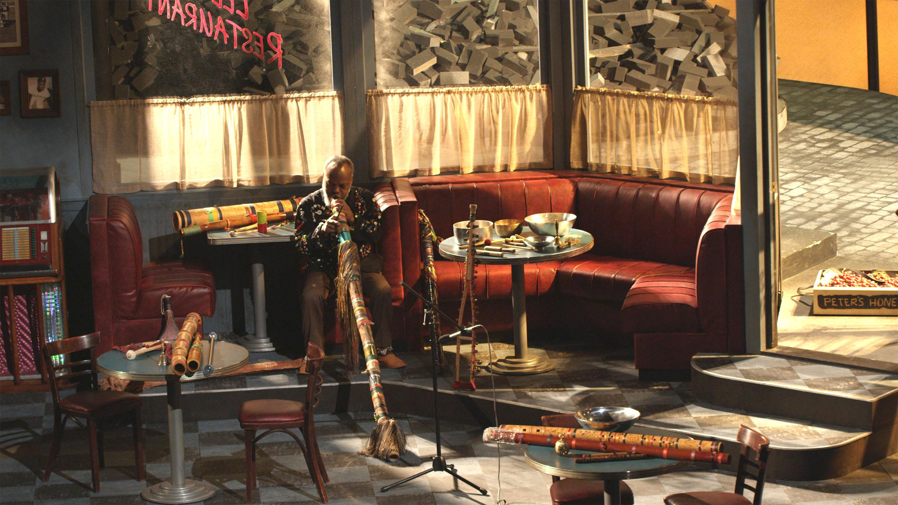 A video still shows a man playing a didgeridoo in a cafe with multiple wind and percussive instruments on tabletops.