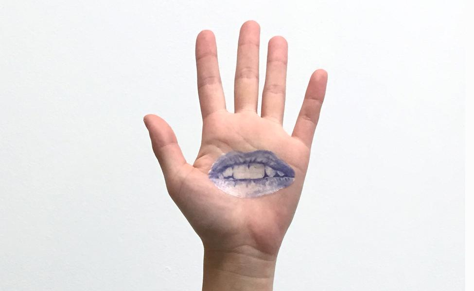 The palm of a hand faces the camera in front of a white backdrop. Inside the palm of the hand is a blue and white illustration of a half opened mouth.