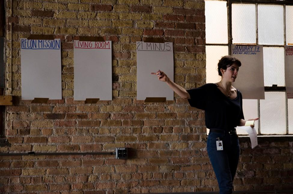 """Lyra Hill speaks in front of a series of posters hung along a brick wall. The signs read: """"Recon Mission"""", """"Living Room"""", and """"21 Minus""""."""