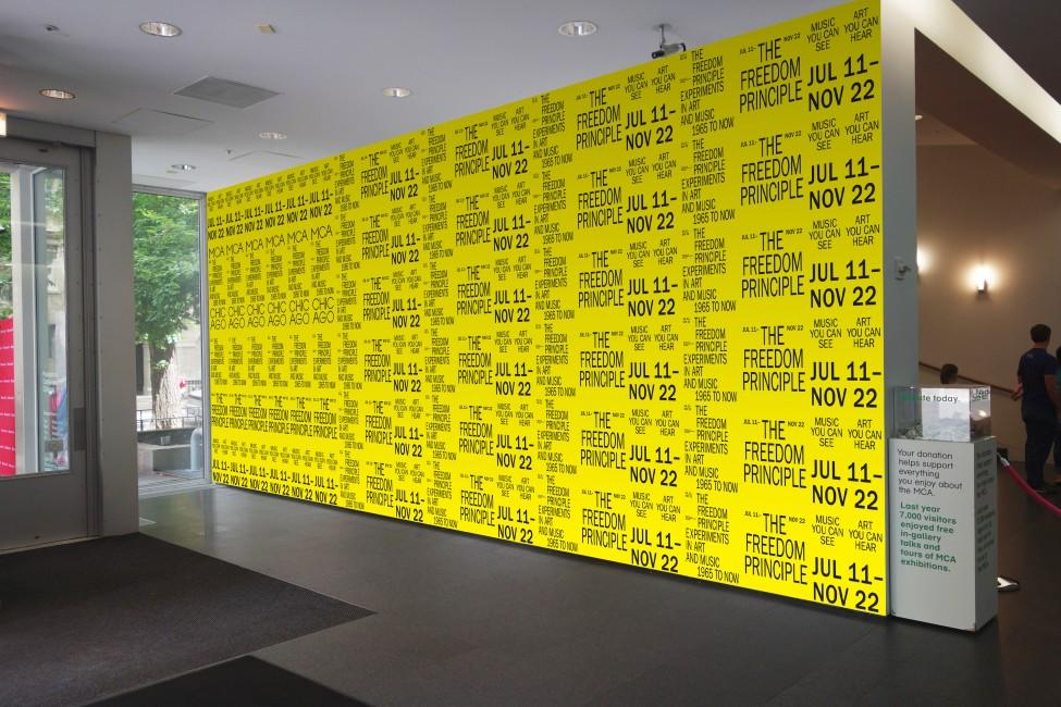 Bright yellow wall covered with rows of repeated black text stating the title and dates of the MCA exhibition *The Freedom Principle*