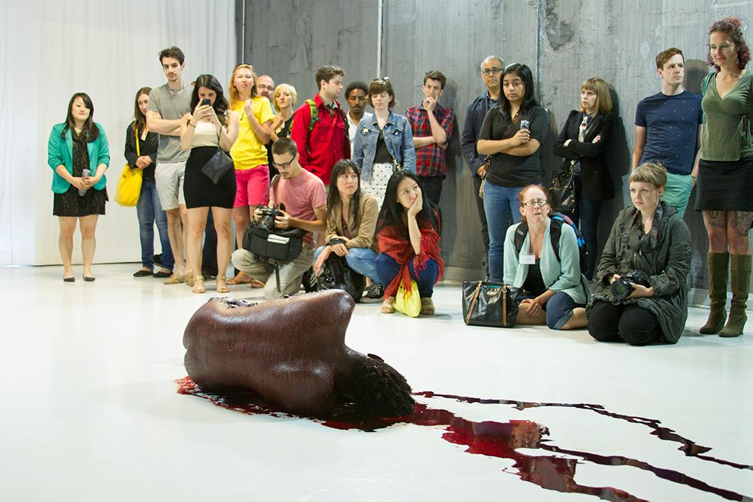 A naked performer smeared with blood is curled in the fetal position, facing a small audience.