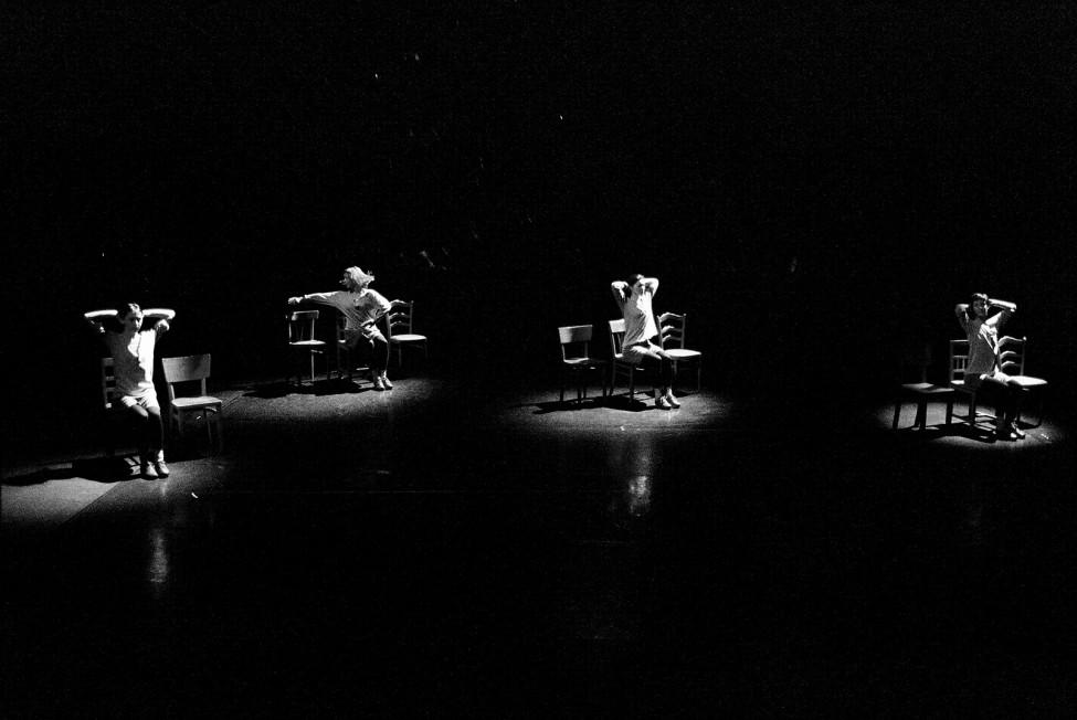 Black-and-white performance still of four women on a pitch-black stage, each one illuminated by a spotlight and dancing in a chair