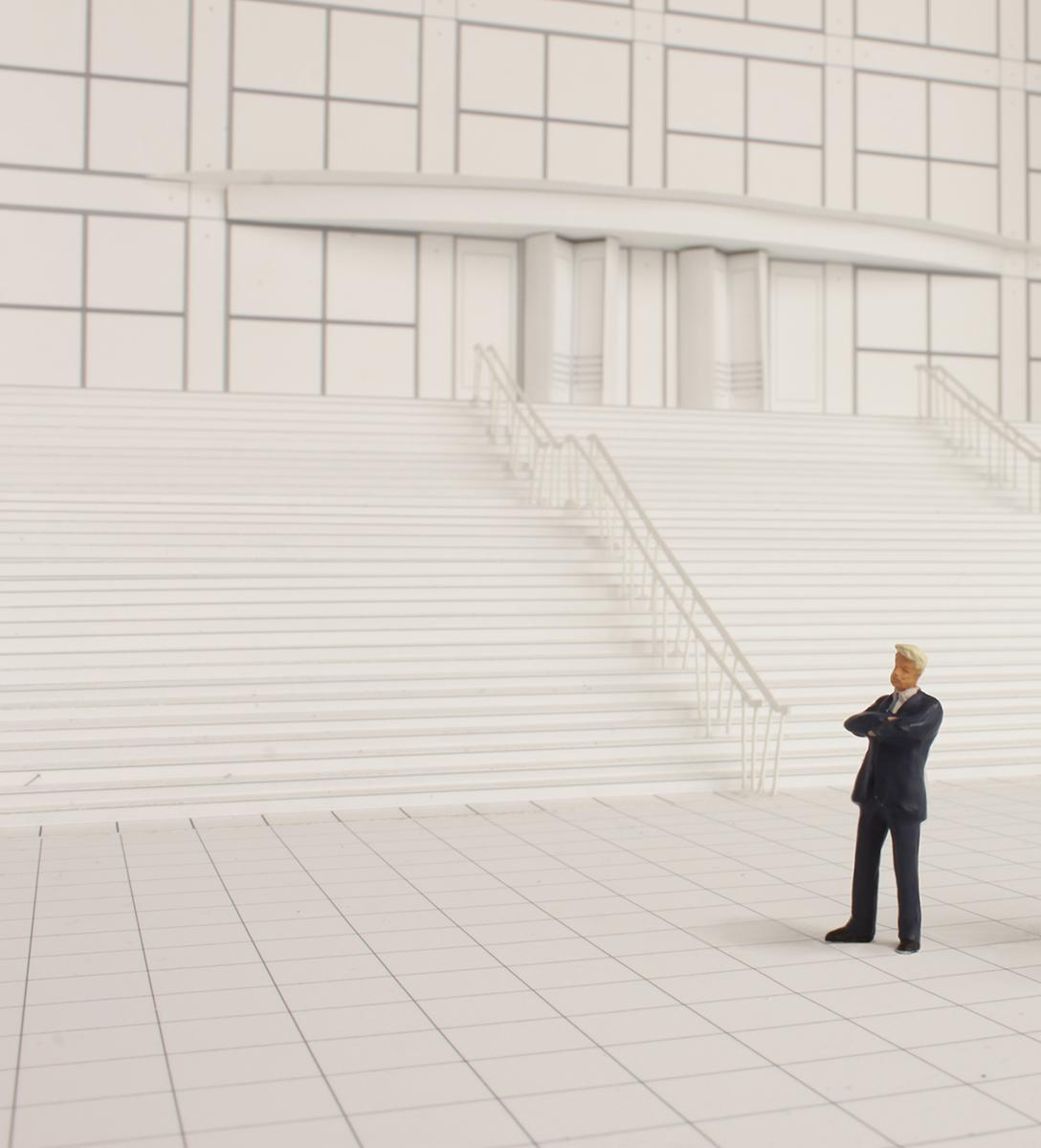 A black-and-white model of the MCA's front staircase with a male figurine in a black suit standing on the plaza.