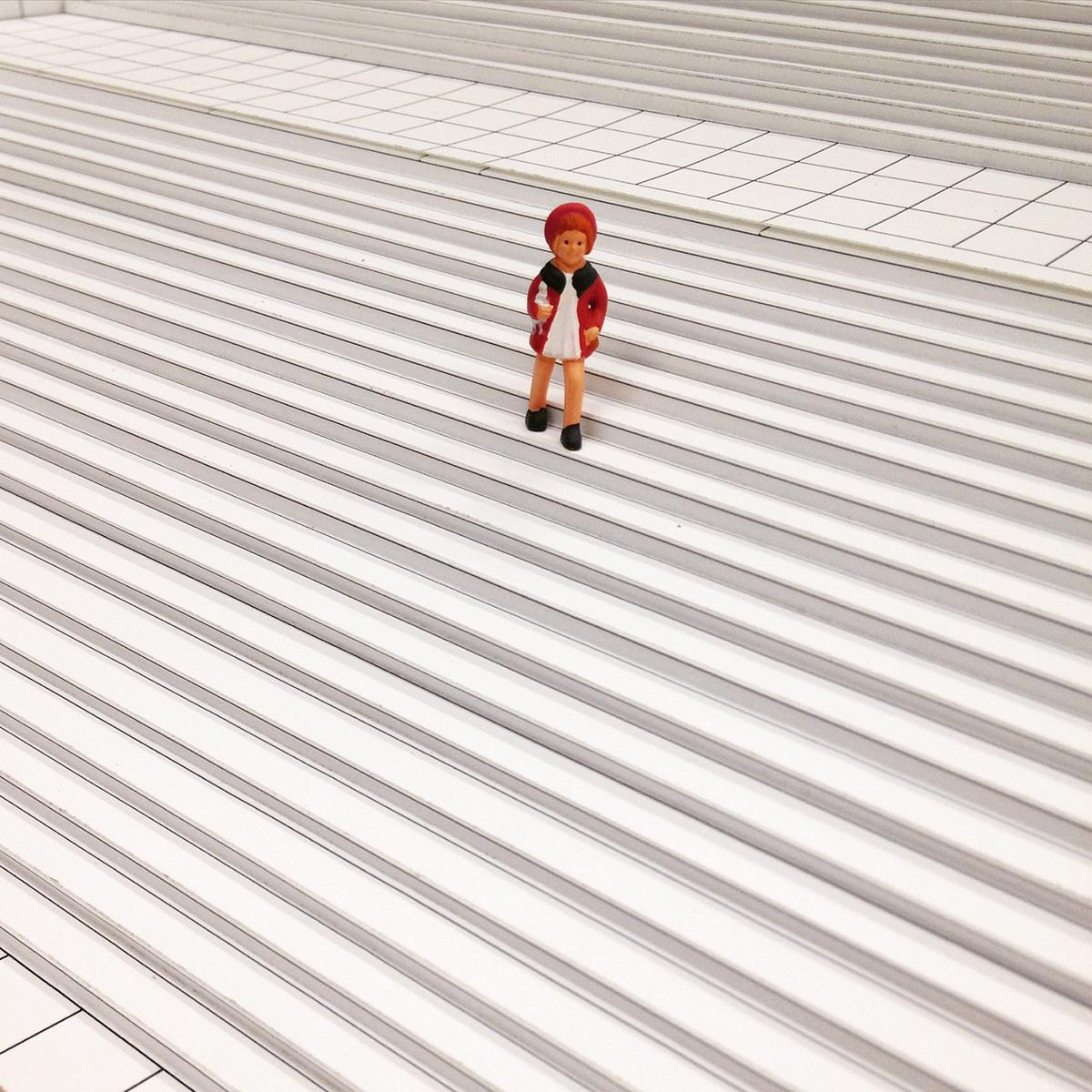 A close-up of a black-and-white model of the MCA's front stairs with a little girl figurine in a white dress and a red jacket and beret.