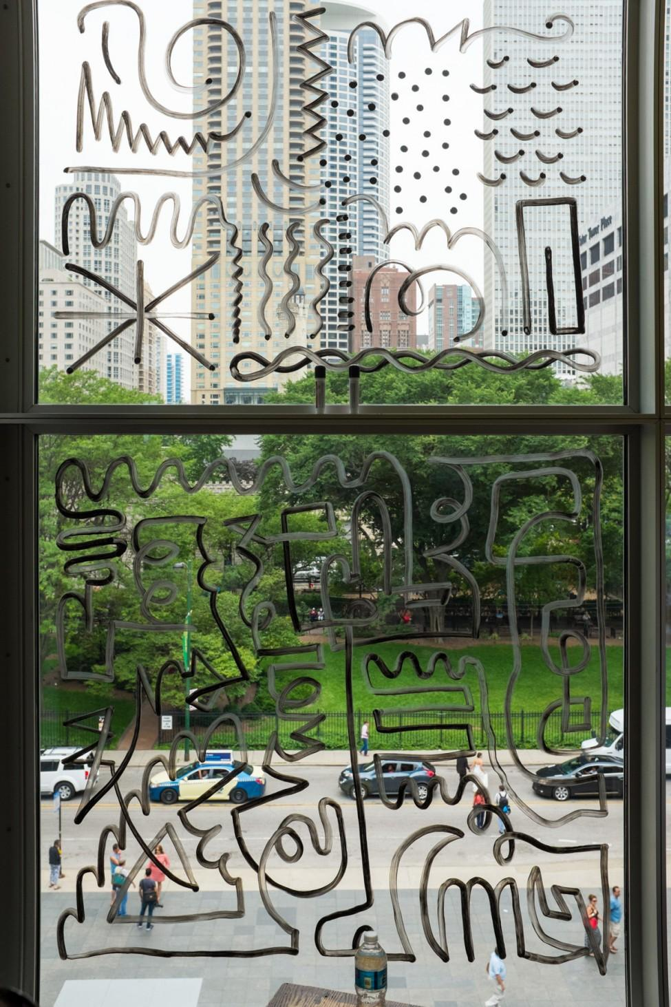 Various doodles in black marker appear on a window which looks out onto a lush park and tall buildings.