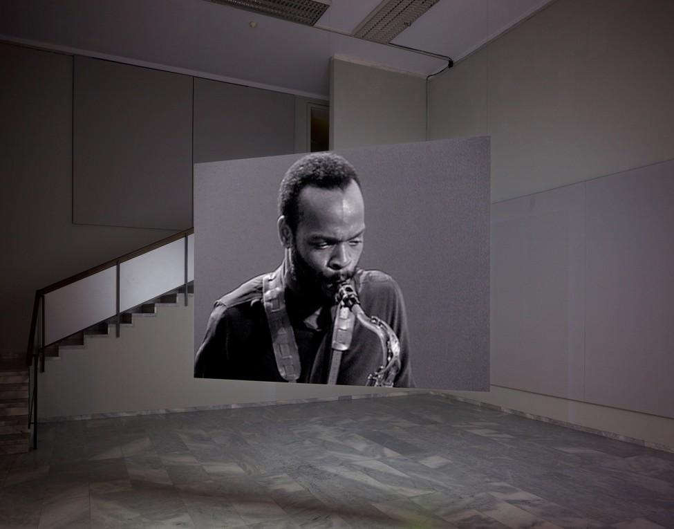 Installation view of a screen suspended from the ceiling with a video projection of a man playing the saxaphone