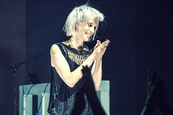 Artist St. Vincent stands smilingly on stage. Her silver hair is tousled, and she is wearing a beaded black dress.