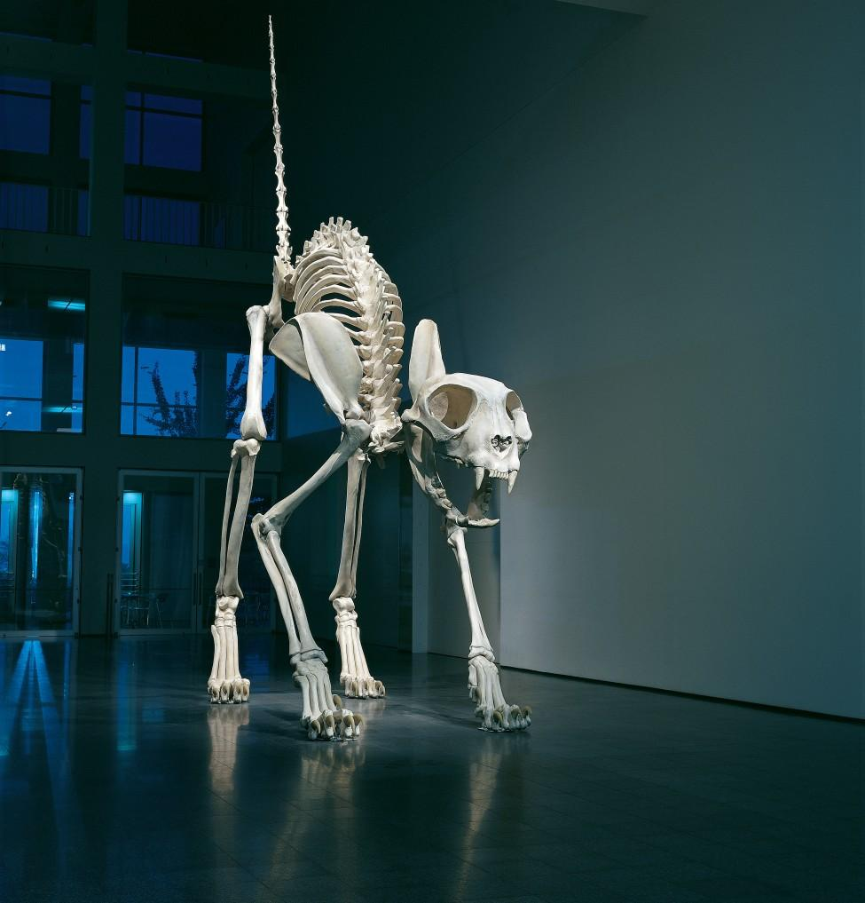 A gigantic cat skeleton stands with its back arched and tail pointed straight up in the air.