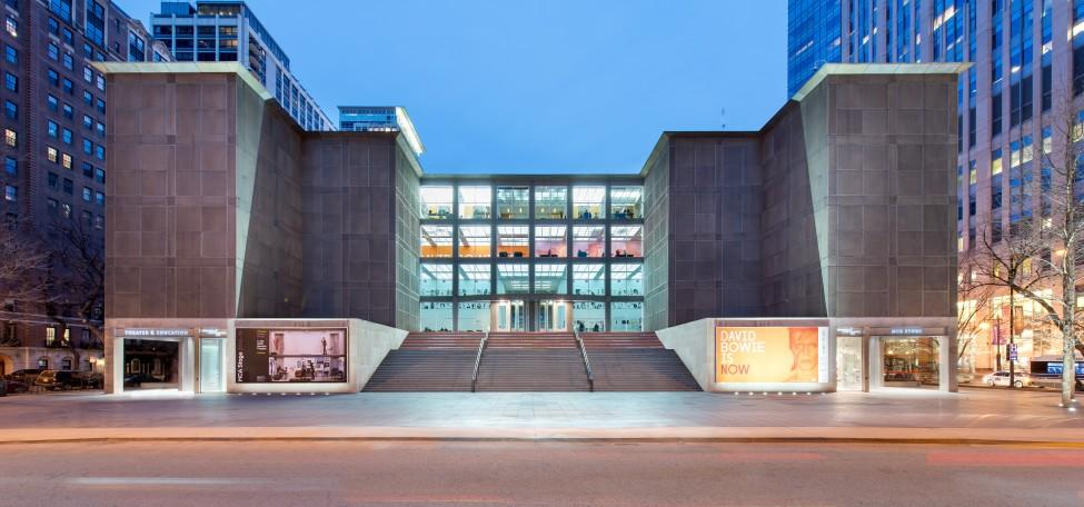 The front of the MCA is lit up at dusk, photographed from across Mies van der Rohe Street.